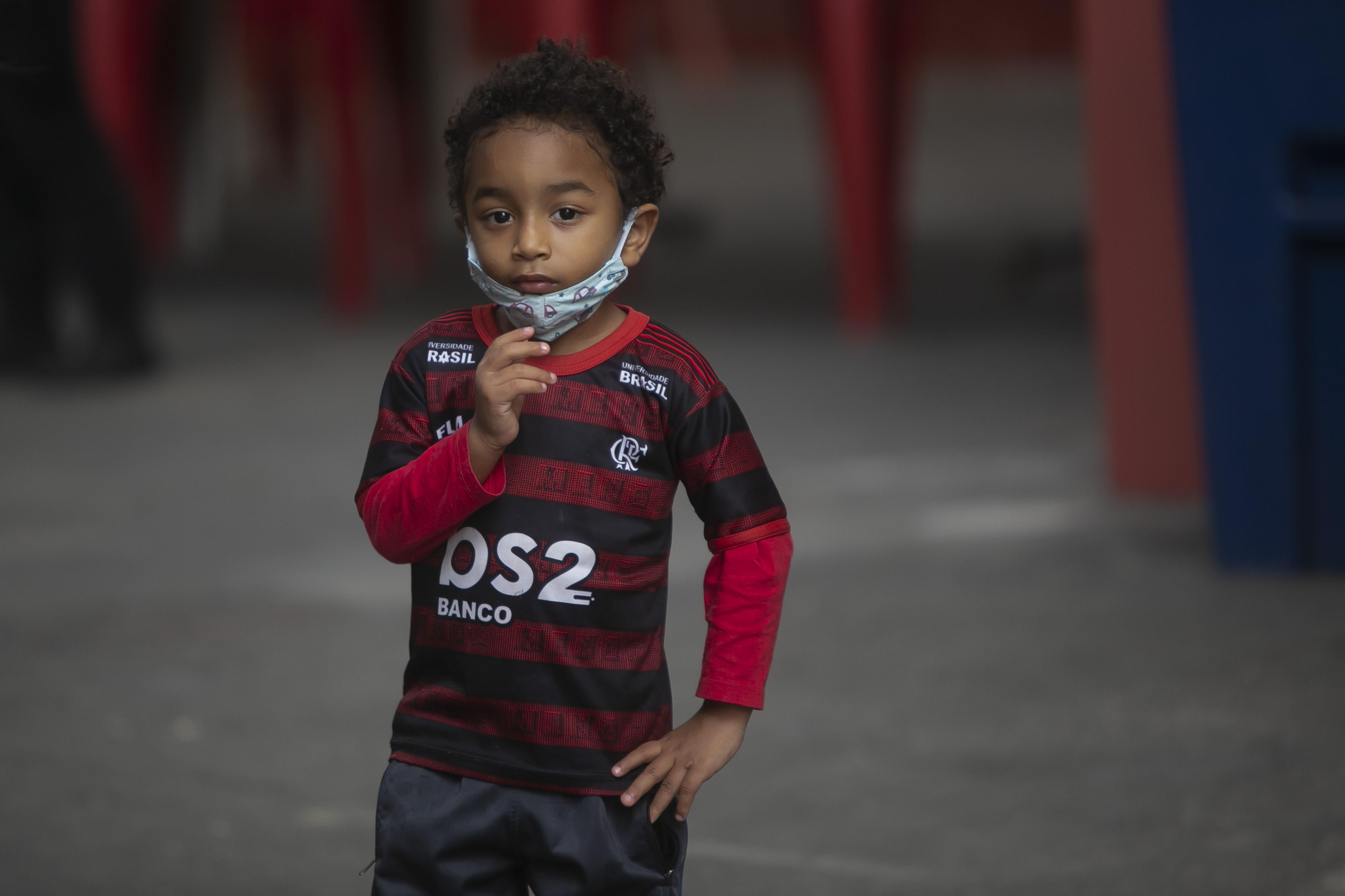RIO DE JANEIRO, BRAZIL - JUNE 05: The son of a member of the 'Torcida Urubuzada' (soccer fans) of Flamengo looks on during the donation of food amidst the coronavirus (COVID-19) pandemic in the Tijuca neighborhood on June 5, 2020 in Rio de Janeiro, Brazil. Around 100 packs of food were distributed by the 'Torcida Urubuzada' of Flamengo to self-employed stadium vendors. According to the Brazilian Health Ministry, Brazil has over 630,000 positive cases of coronavirus (COVID-19) and more than 34,600 deaths. (Photo by Bruna Prado/Getty Images)