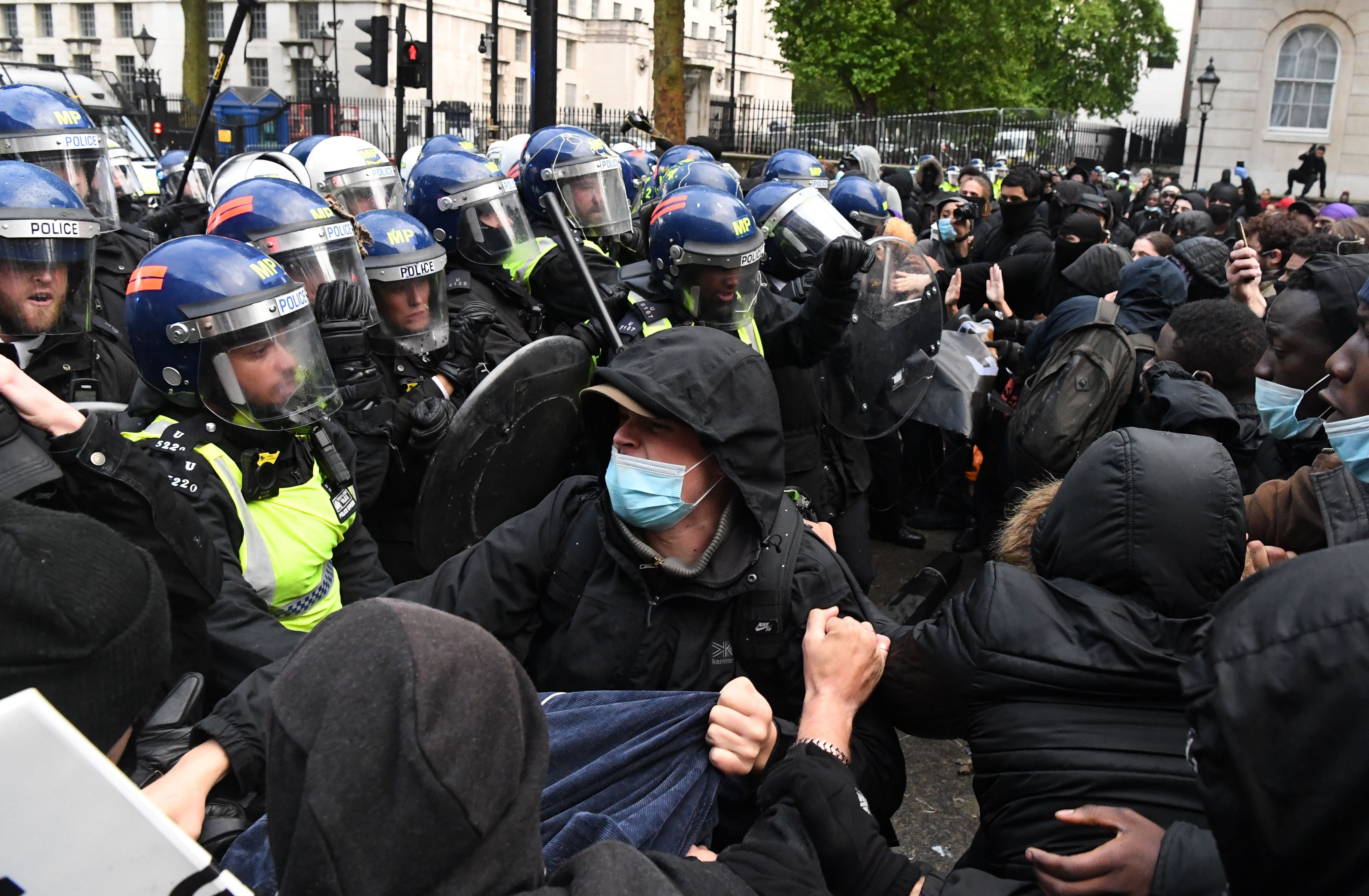 """Protestors, some wearing PPE (personal protective equipment), including a face mask as a precautionary measure against COVID-19,  scuffle with Police officers in riot gear near Downing Street, in central London on June 6, 2020, during a demonstration organised to show solidarity with the Black Lives Matter movement in the wake of the killing of George Floyd, an unarmed black man who died after a police officer knelt on his neck in Minneapolis. - The United States braced Friday for massive weekend protests against racism and police brutality, as outrage soared over the latest law enforcement abuses against demonstrators that were caught on camera. With protests over last week's police killing of George Floyd, an unarmed black man, surging into a second weekend, President Donald Trump sparked fresh controversy by saying it was a """"great day"""" for Floyd. (Photo by DANIEL LEAL-OLIVAS / AFP) (Photo by DANIEL LEAL-OLIVAS/AFP via Getty Images)"""