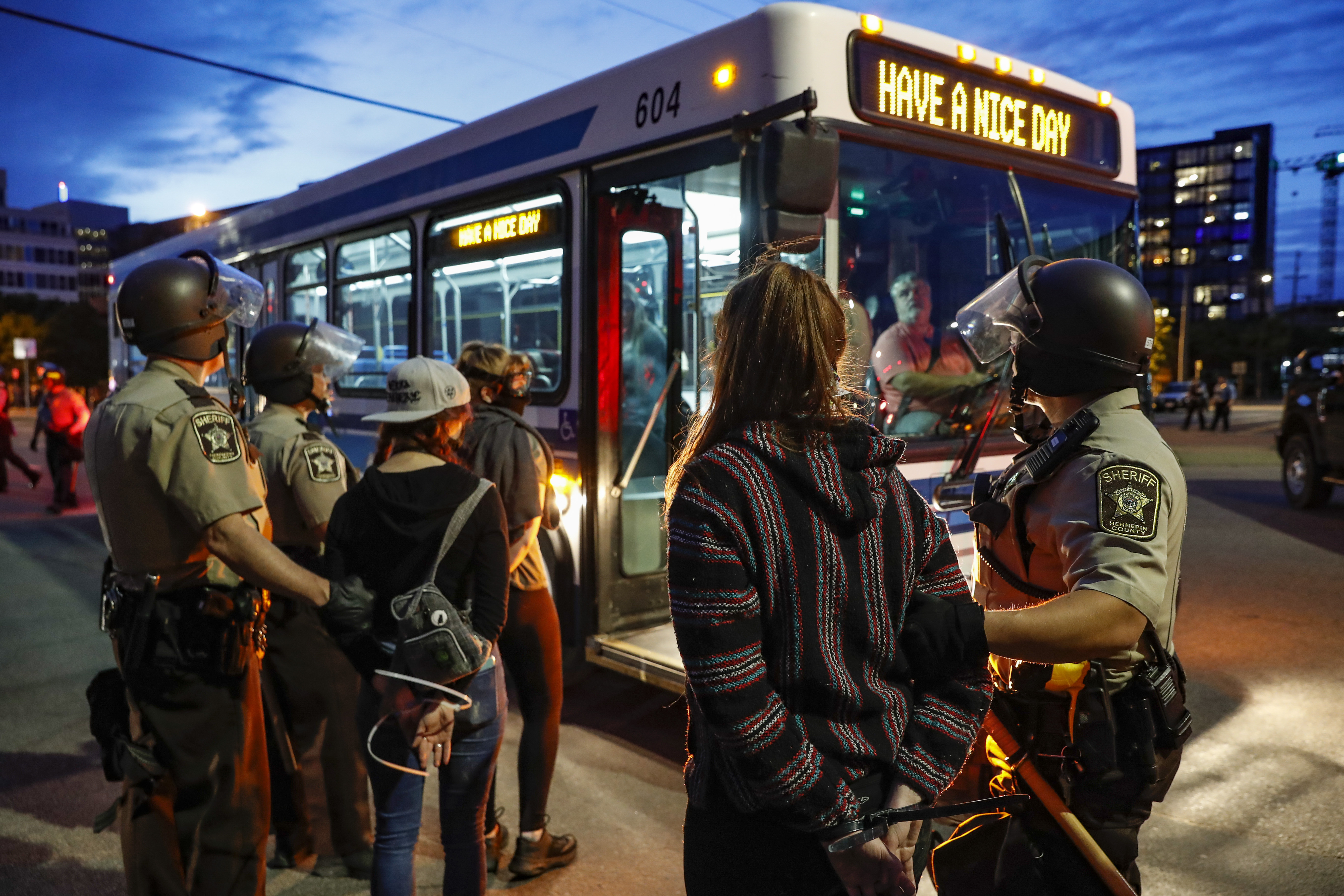 Arrested protesters are loaded onto a transport bus by police on South Washington Street, Sunday, May 31, 2020, in Minneapolis. Protests continued following the death of George Floyd, who died after being restrained by Minneapolis police officers on Memorial Day. (AP Photo/John Minchillo)