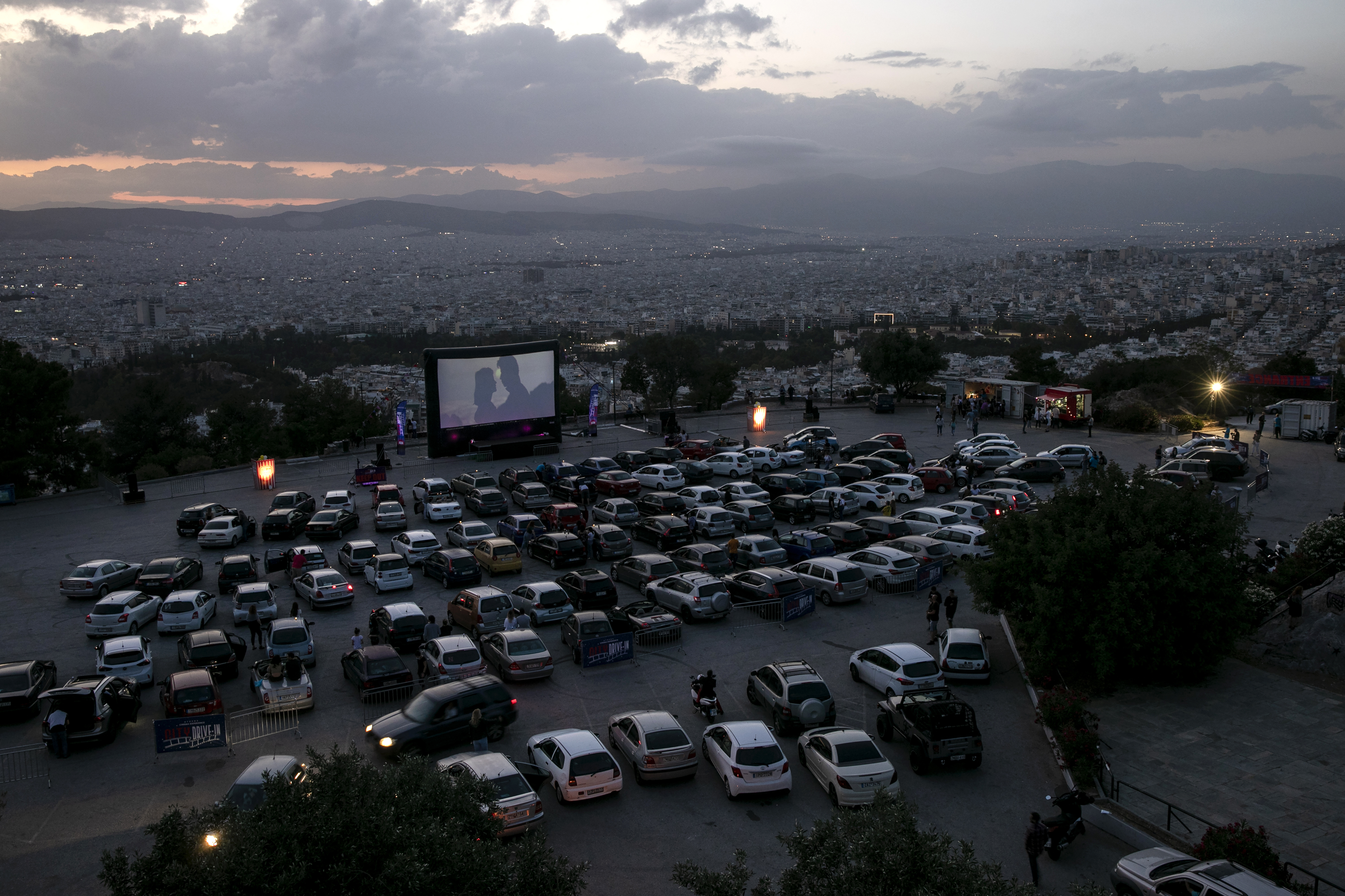 """Moviegoers watch the film """"Grease"""" at the Lycabettus Hill drive-in cinema as the measures against coronavirus ease, in Athens, Greece, Saturday, June 6, 2020. (AP Photo/Yorgos Karahalis)"""
