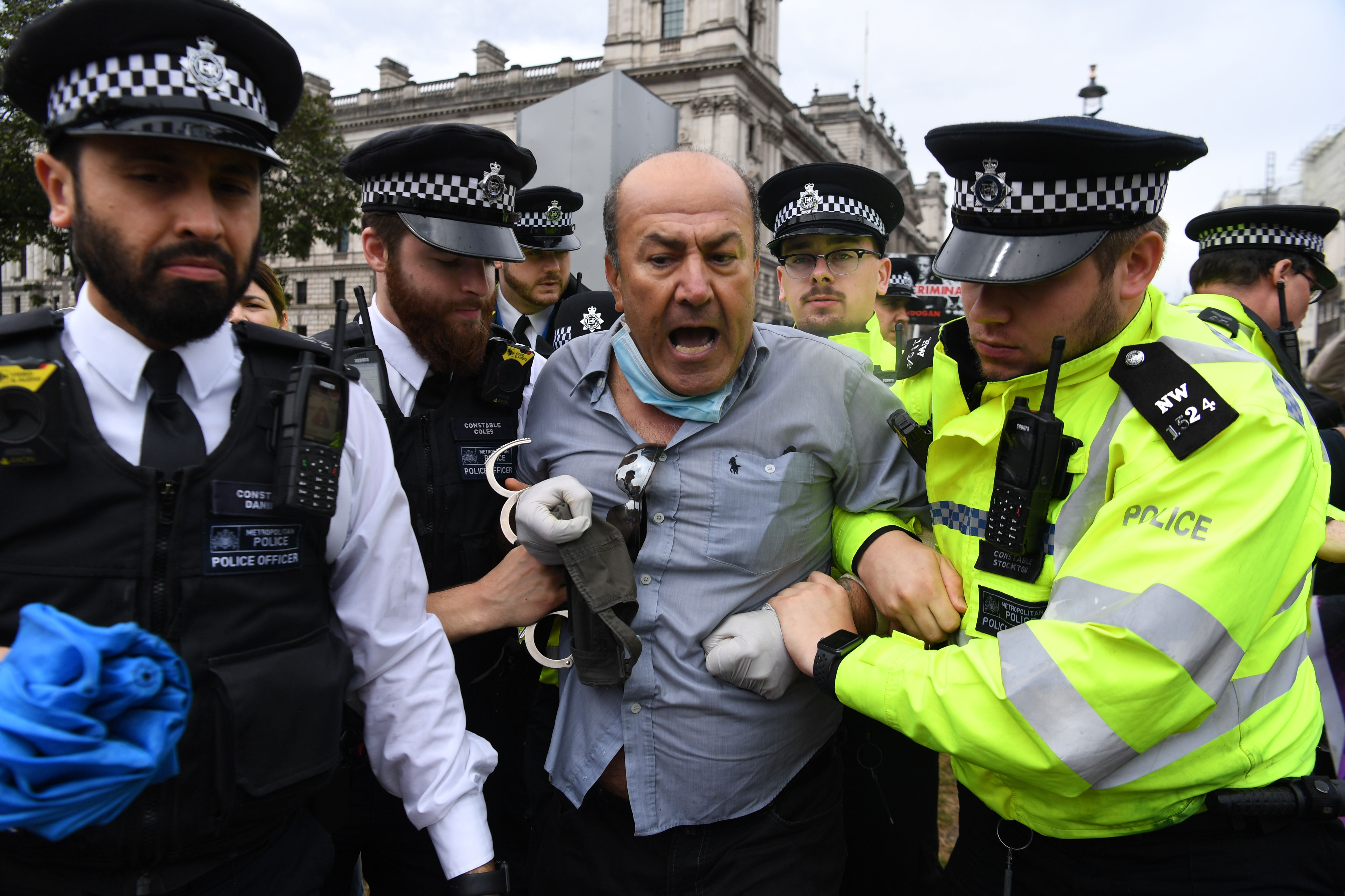 A pro-Kurdish protester who ran into the road toward the car of Britain's Prime Minister Boris Johnson as it was leaving the Houses of Parliament in London on June 17, 2020 is led away by police officers. - The protester ran into the road towards the Jaguar that normally carries the Prime Minister Boris Johnson and was stopped by police. As the Jaguar stopped it was subsequently struck from behind by the next vehicle in the convoy resulting in a large dent. (Photo by DANIEL LEAL-OLIVAS / AFP) (Photo by DANIEL LEAL-OLIVAS/AFP via Getty Images)
