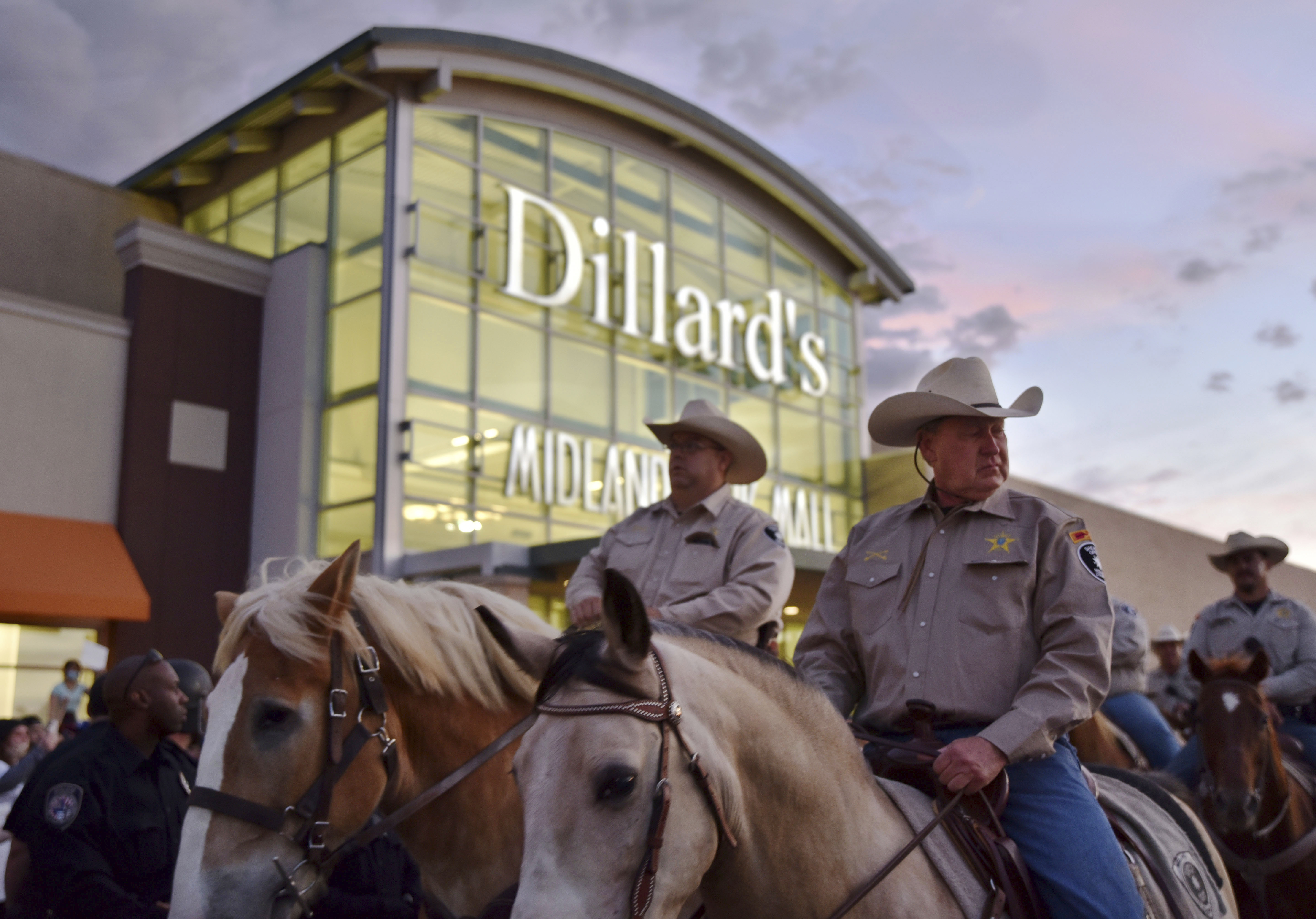 Mounted Midland County sheriff's deputies head through a crowd outside the Midland Park Mall while trying to disperse protesters during a Black Lives Matter demonstration in Midland, Texas, on Sunday, May 31, 2020, following the May 25 death of George Floyd, who was pinned at the neck by a Minneapolis police officer. (Eli Hartman/Odessa American via AP)