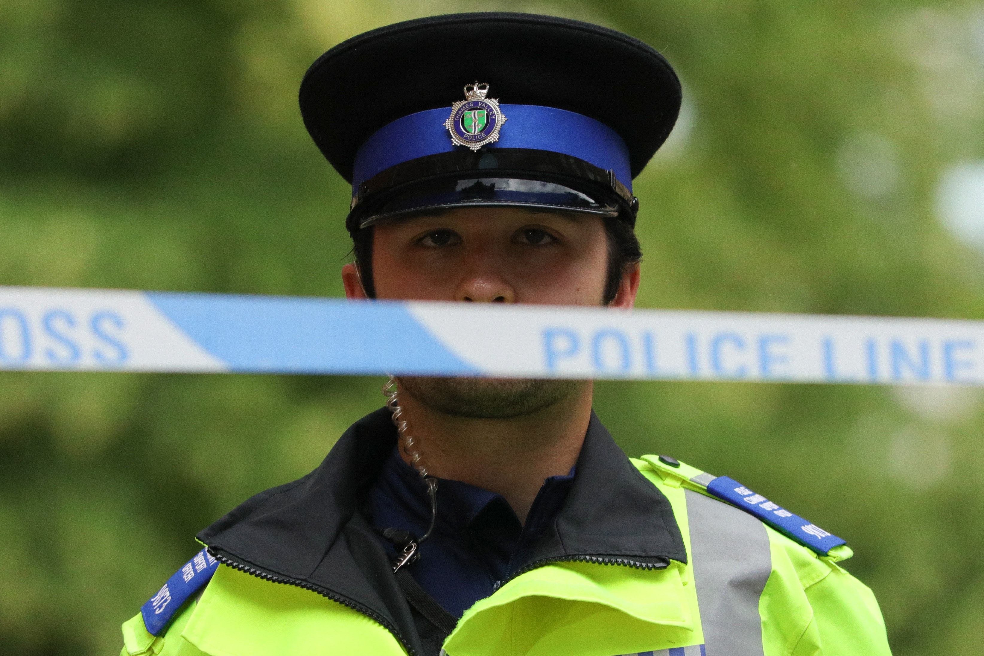 """READING , June 21, 2020  -- A police officer stands behind a police cordon at an entrance to Forbury Gardens where stabbings took place in Reading, Britain, on June 21, 2020. Britain's counter-terrorism police said Sunday that the stabbing incident taking place in southern England's town of Reading on Saturday night """"has now been declared a terrorist incident.""""(Photo by Tim Ireland/Xinhua via Getty) (Xinhua/ via Getty Images)"""