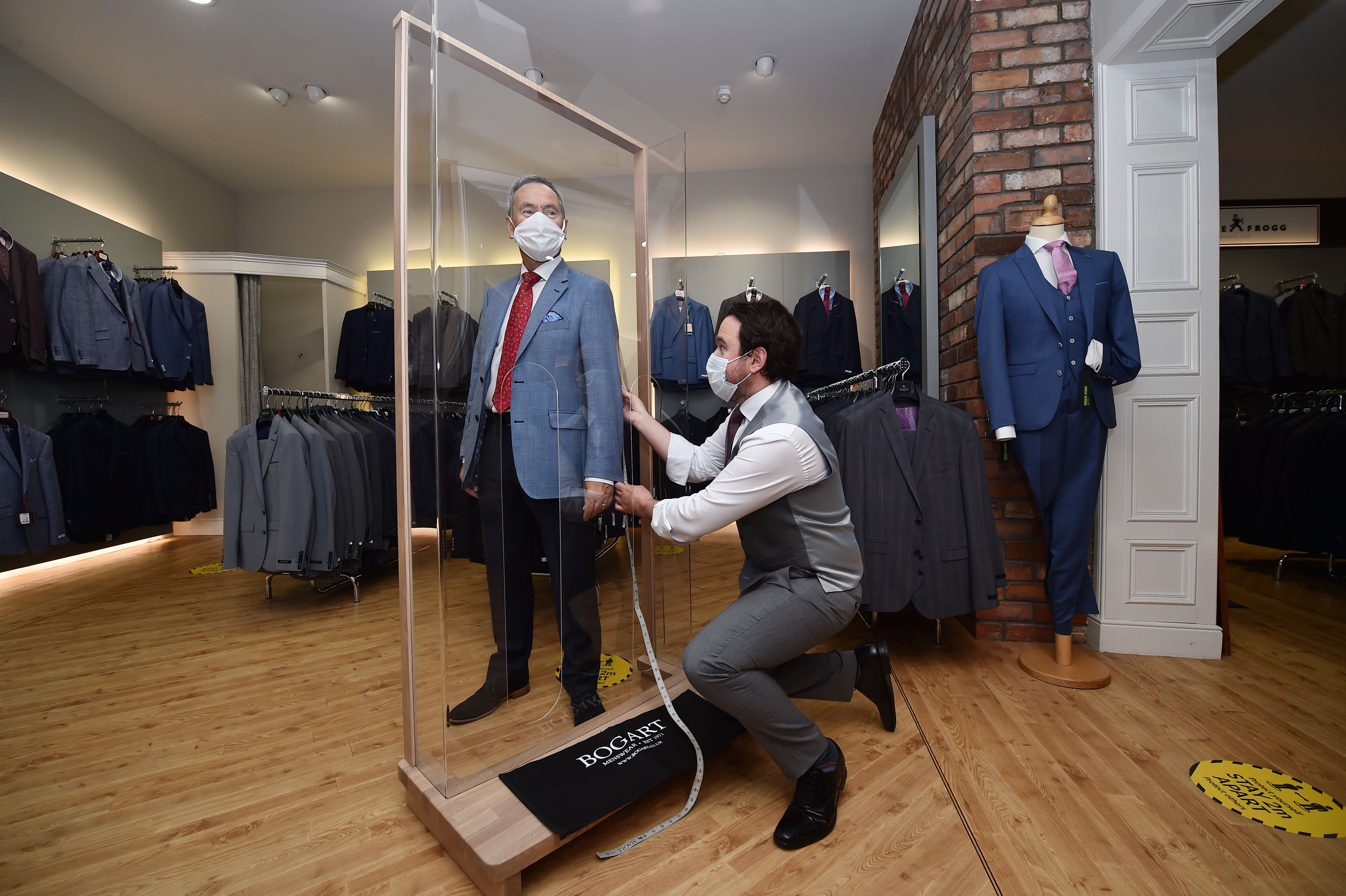 BELFAST, NORTHERN IRELAND - JUNE 12: Tailor Gary Keenan (R) of Bogart Menswear measures up a suit using a customer pod designed to keep customers safe from Covid-19 after their store reopened for business on June 12, 2020 in Belfast, Northern Ireland. After being shuttered for months to curb the spread of Covid-19, retailers here reopened with social distancing measures, a few days ahead of when similar businesses can reopen in England. (Photo by Charles McQuillan/Getty Images)