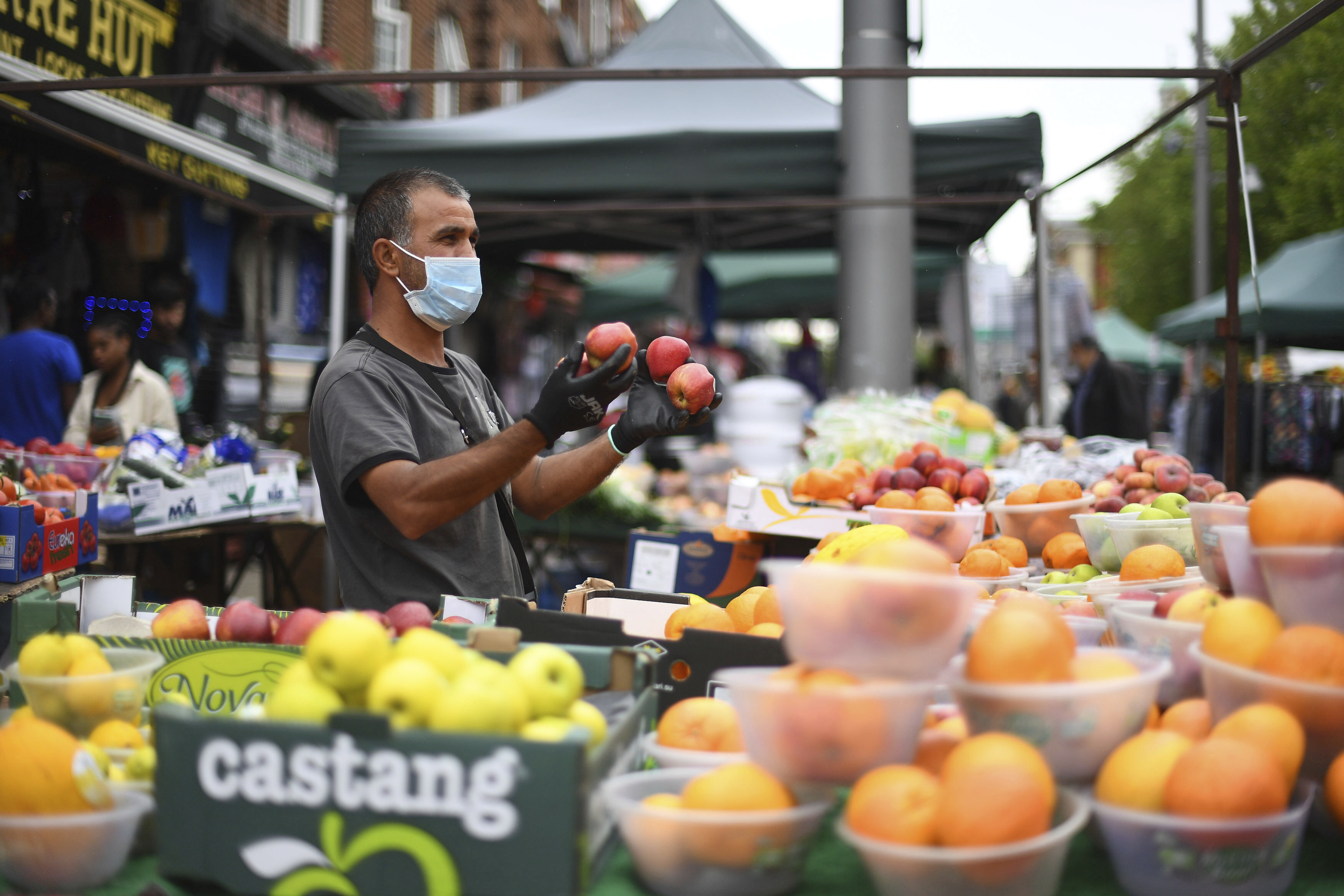 Stalls reopen at Walthamstow Market in east London, the longest street market in Europe, following the introduction of measures to bring England out of lockdown, Wednesday June 3, 2020.  The highly contagious COVID-19 coronavirus has impacted on Britain with self isolation and social distancing when people move from their homes. (Victoria Jones / PA via AP)