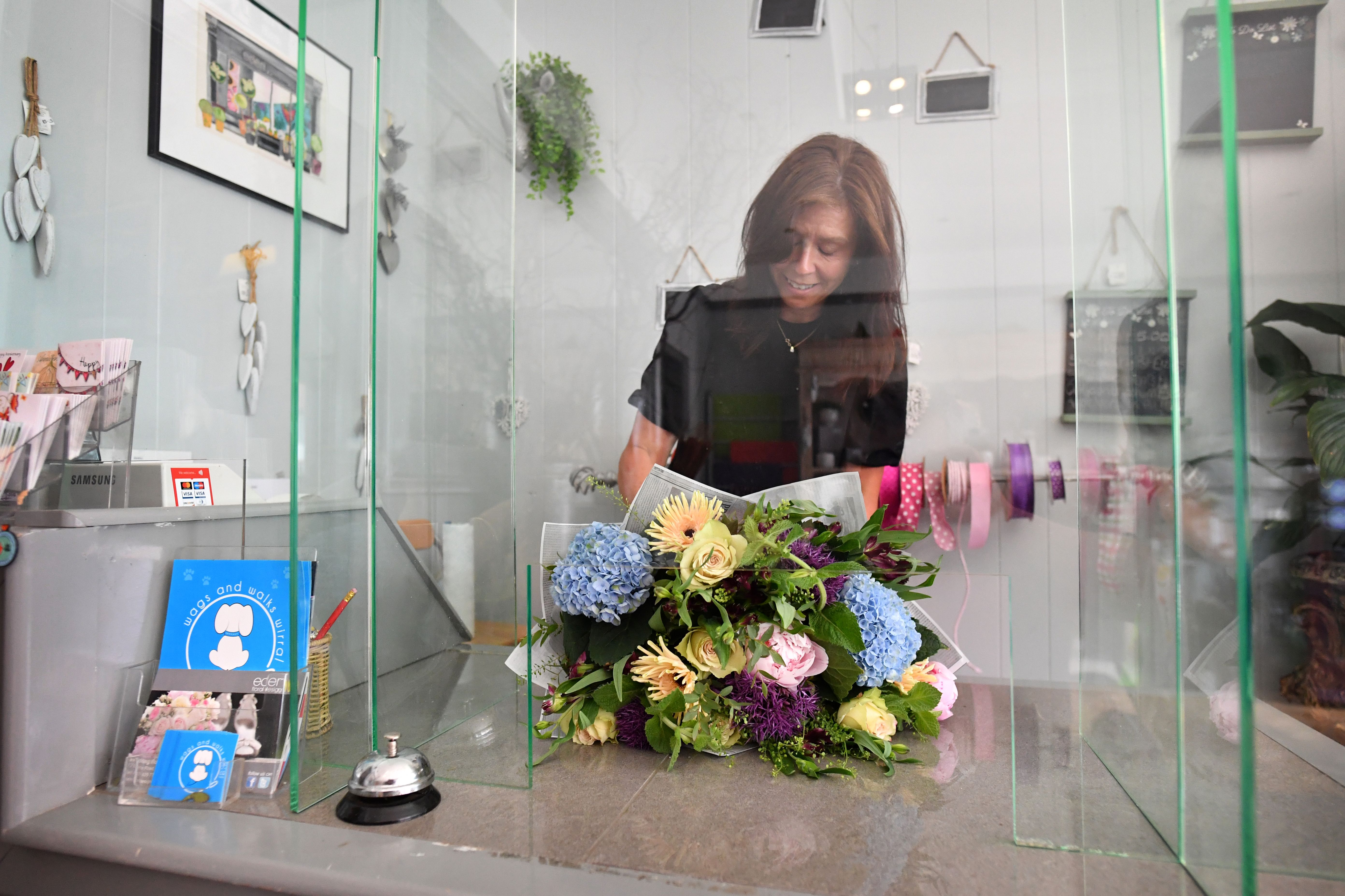 Florist Trish Collins-Morgan works behind a plastic screen as she re-opens her shop, with various safety policies in place, in West Kirby north west England on June 17, 2020, as lockdown restrictions are eased during the novel coronavirus COVID-19 pandemic. - Various stores and outdoor attractions in England opened Monday for the first time in nearly three months, as the government continues to ease its coronavirus lockdown. (Photo by Paul ELLIS / AFP) (Photo by PAUL ELLIS/AFP via Getty Images)