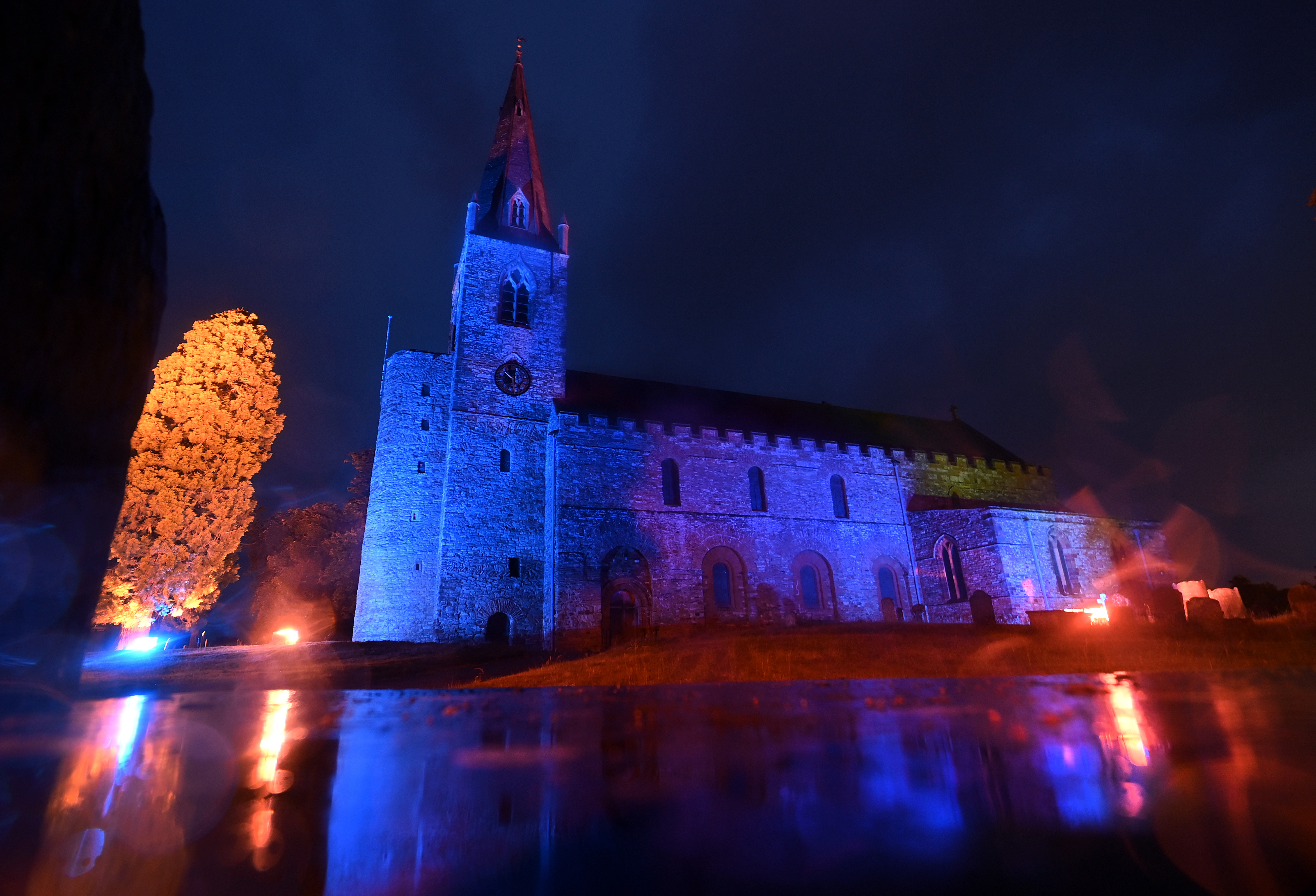 BRIXWORTH - JUNE 04: All Saints Anglo Saxon Church is lit up in blue in support of the NHS on June 04, 2020 in Brixworth, England. The British government further relaxed Covid-19 quarantine measures in England this week, allowing groups of six people from different households to meet in parks and gardens, subject to social distancing rules. Many schools also reopened and vulnerable people who are shielding in their homes are allowed to go outside again. (Photo by Clive Mason/Getty Images)