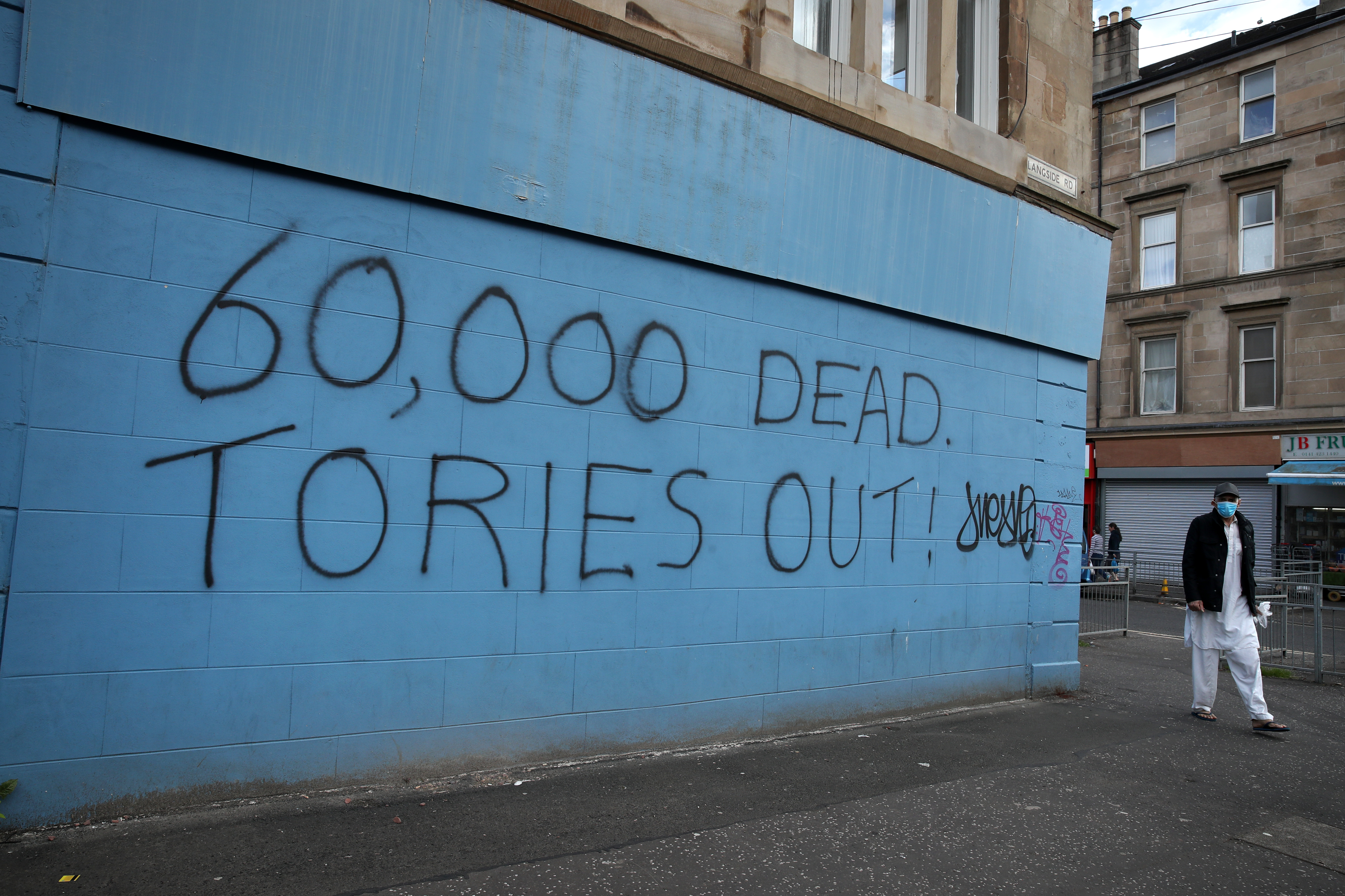 A person passes coronavirus related graffiti in Glasgow as Scotland is moving into phase one of the Scottish Government's plan for gradually lifting lockdown. (Photo by Andrew Milligan/PA Images via Getty Images)