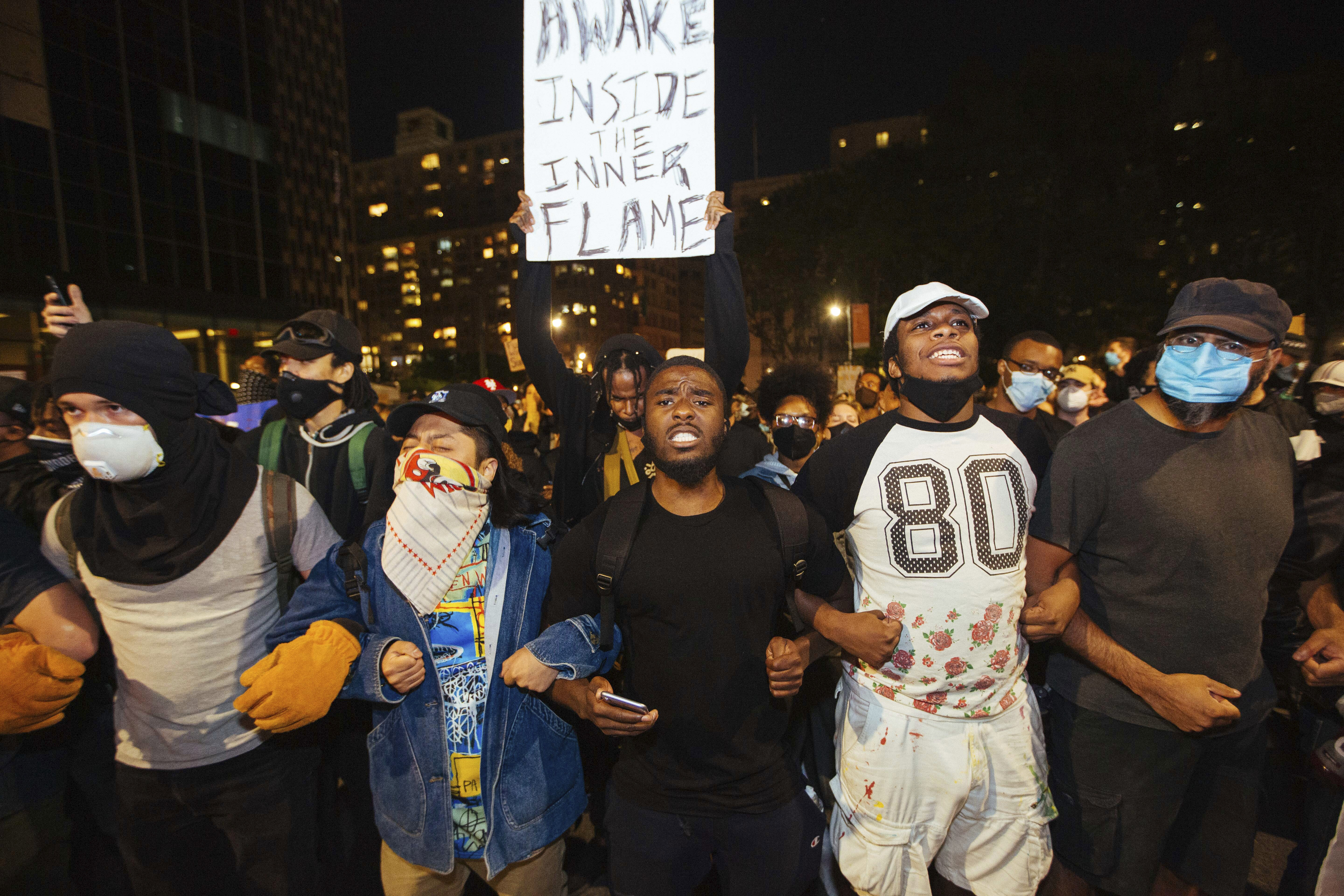 Activists march to the Brooklyn Bridge on Sunday, May 31, 2020, in New York. Demonstrators took to the streets of New York City to protest the death of George Floyd, who died May 25 after he was pinned at the neck by a Minneapolis police officer. (AP Photo/Kevin Hagen).