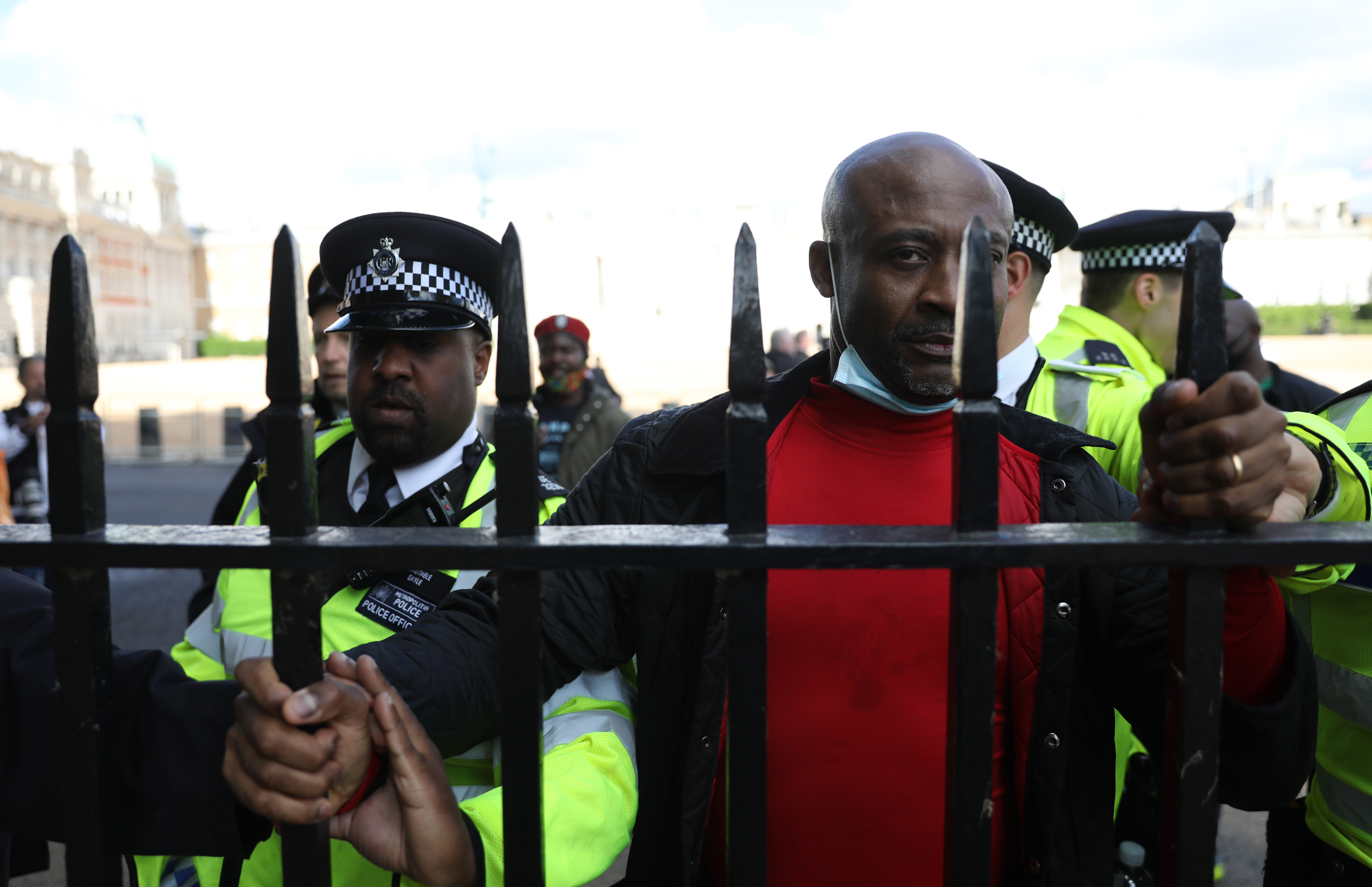 Police restrain a demonstrator who ran after Emmanuel Macron's car convoy as a protest against French interference in Cameroon domestic affairs. The French president was attending an official event with British Prime Minister Boris Johnson during his visit to the UK to mark the 80th anniversary of French Resistance leader Charles de Gaulle's wartime broadcast. Picture date: Thursday June 18, 2020.