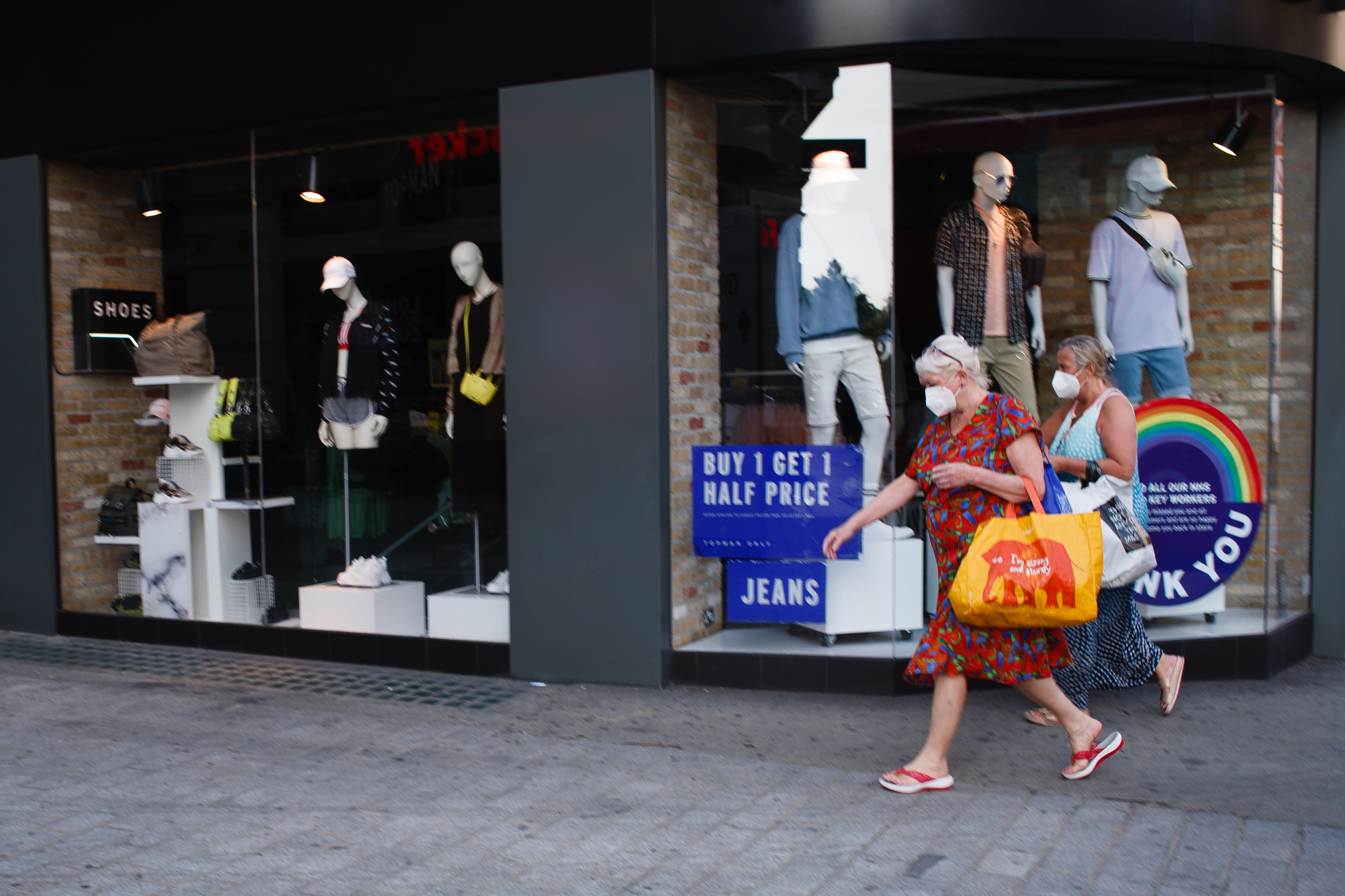 A pair of women wearing face masks turn onto Old Quebec Street from Oxford Street in London, England, on June 23, 2020. British Prime Minister Boris Johnson announced today that the next stage of lockdown easing in England would proceed on schedule, with pubs, restaurants, hotels, hairdressers, theatres, cinemas, museums, galleries, libraries, theme parks and zoos allowed to reopen from July 4. The two-metre social distancing rule is also to be halved from the same date, with people encouraged to take additional mitigation actions, such as wearing face coverings, when close together. The change, to what is being dubbed 'one-metre plus', is seen as key to the survival of the hospitality sector. (Photo by David Cliff/NurPhoto via Getty Images)
