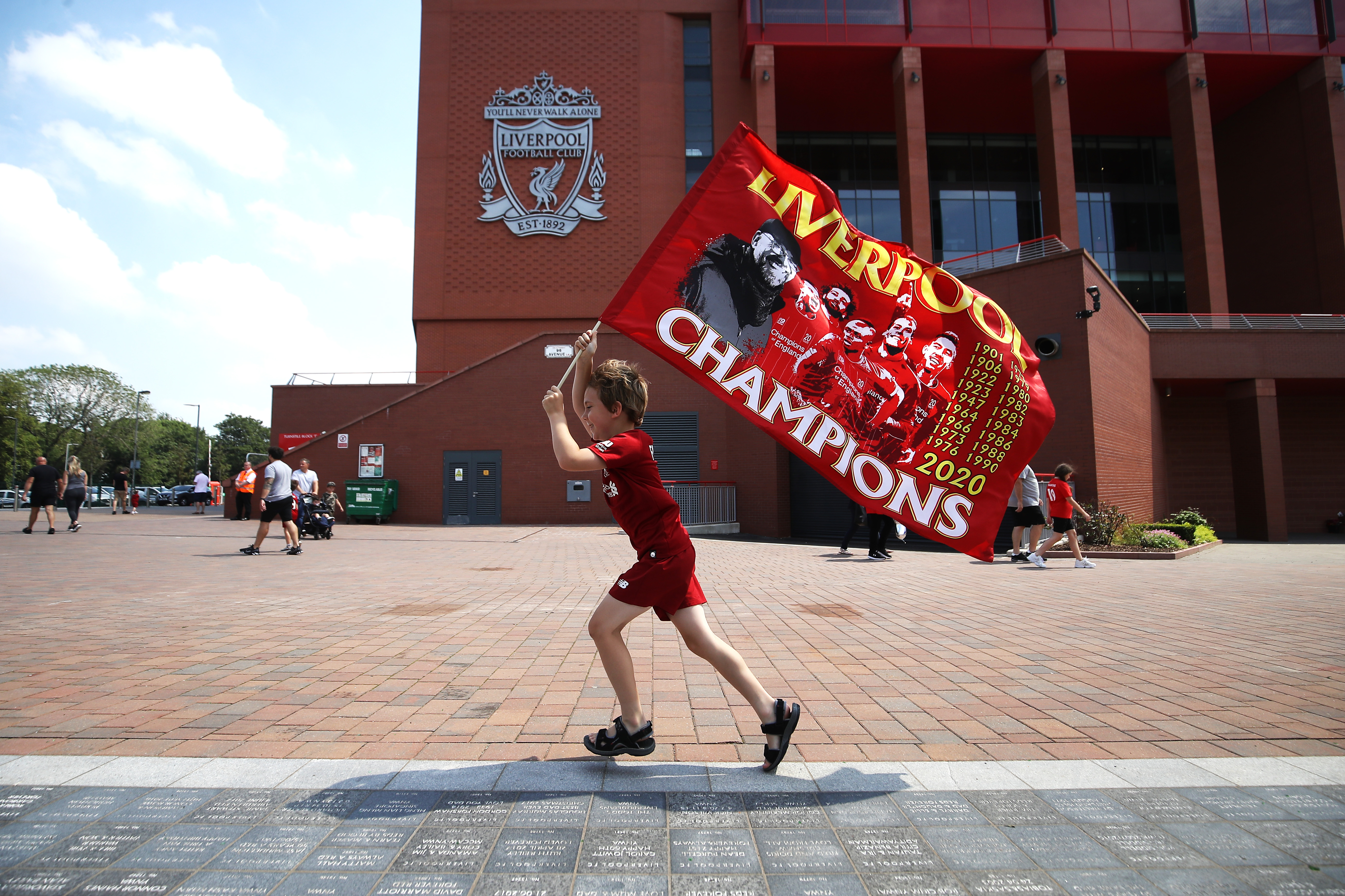 Liverpool fan Dillon Parry waves a flag outside Anfield in Liverpool. (Photo by Martin Rickett/PA Images via Getty Images)