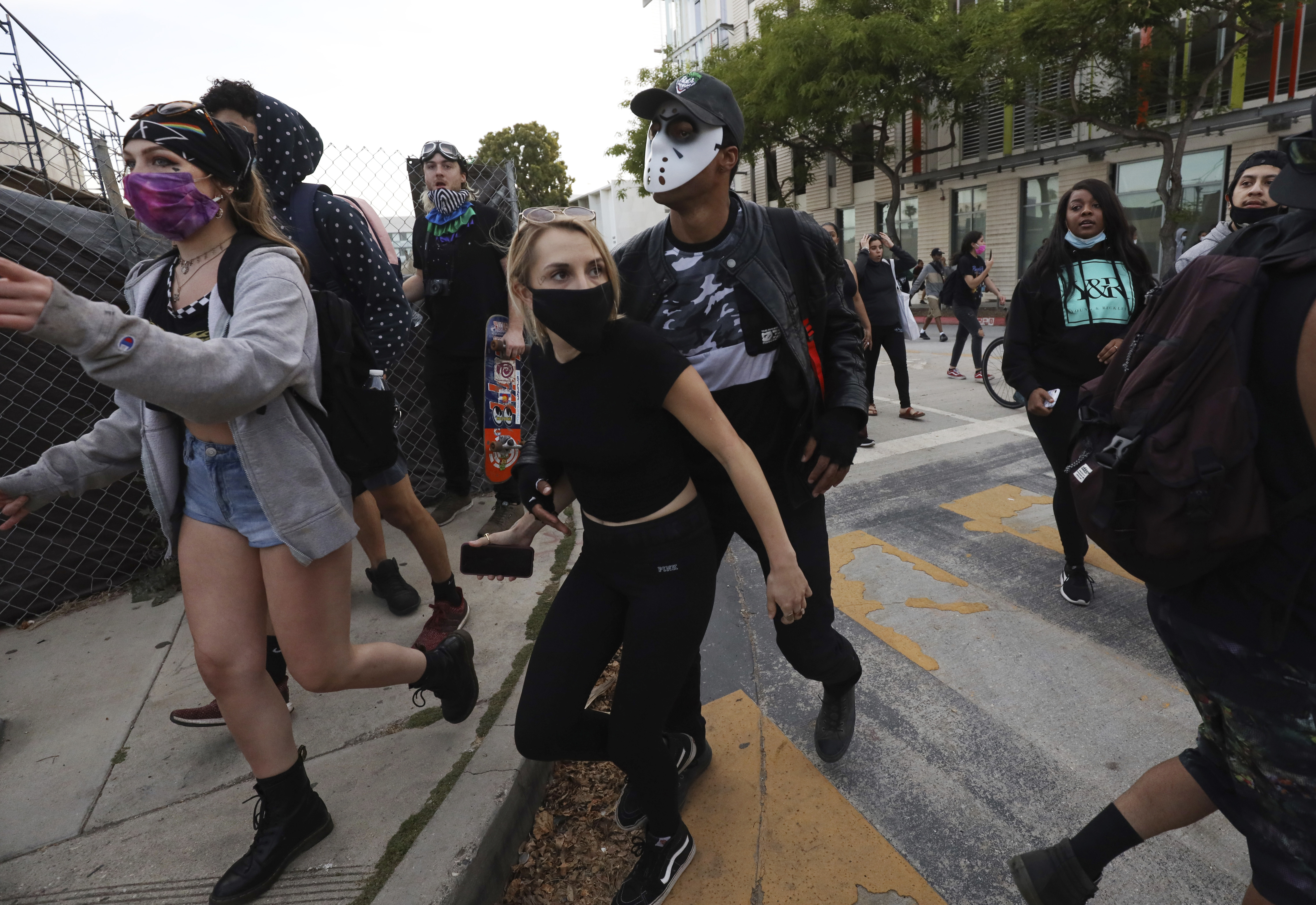 Protesters head away from police in Santa Monica, Calif., Sunday, May 31, 2020, during a demonstration over the death of George Floyd, who died May 25 after he was pinned at the neck by a Minneapolis police officer.  (AP Photo/ Christian Monterrosa)