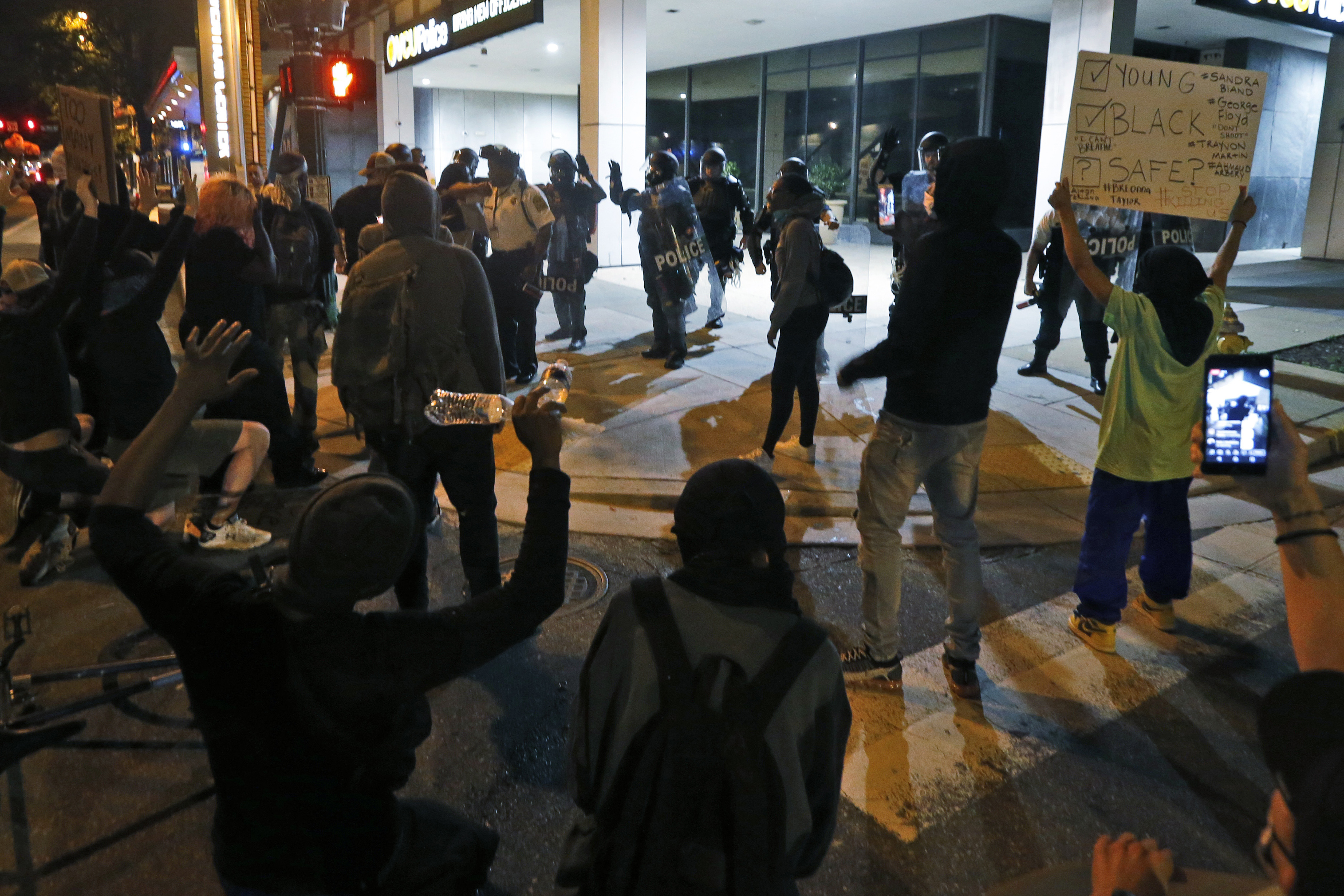 Protesters speak to Virginia Commonwealth University police who expressed solidarity with the marchers during a third night of unrest Sunday May 31, 2020, in Richmond, Va. Gov. Ralph Northam issued a curfew for this evening. (AP Photo/Steve Helber)