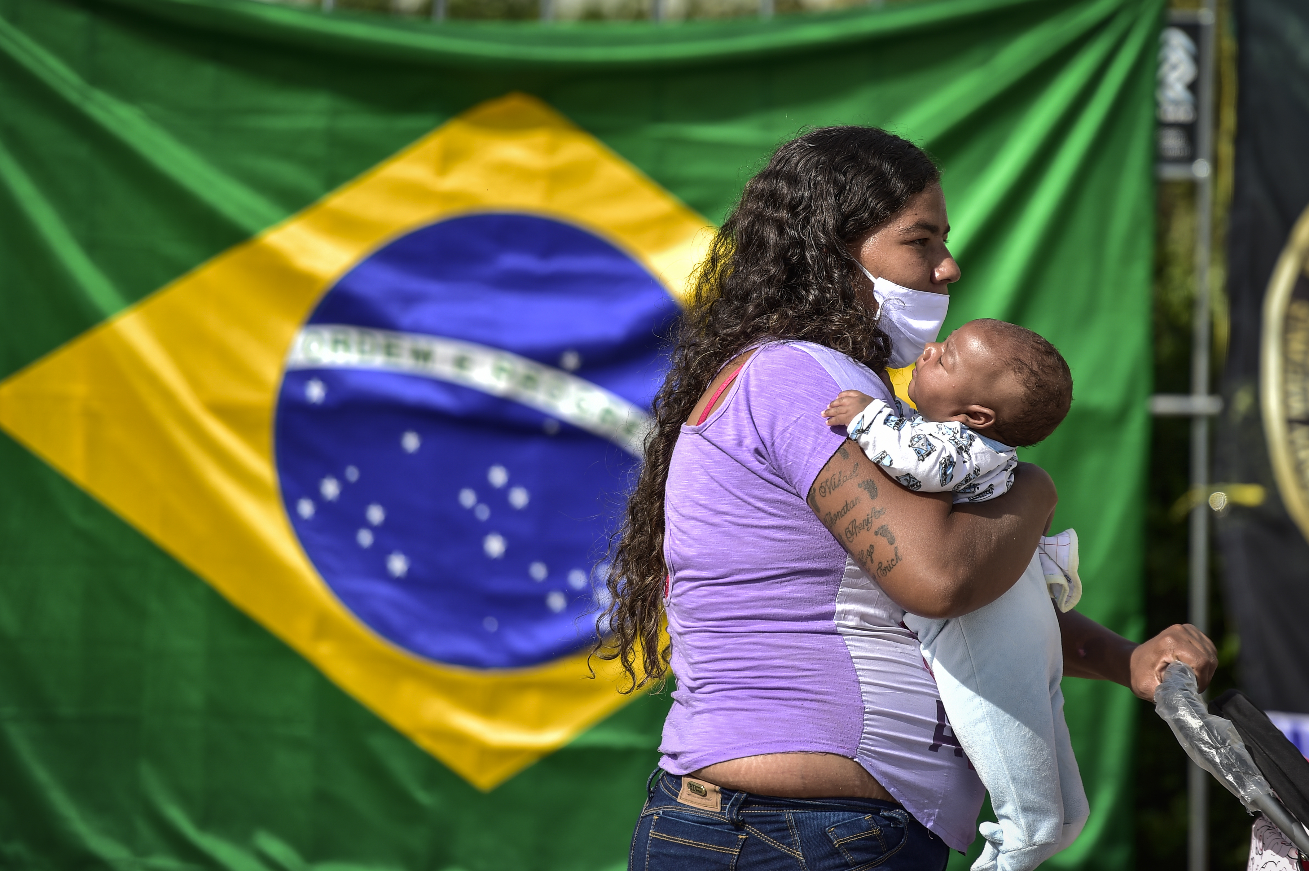 BELO HORIZONTE, BRAZIL - JUNE 05: A woman waits with hel child in line to receive lunch at Praça da Estação on June 5, 2020 in Belo Horizonte, Brazil. About 3000 meals are being distributed every Friday to poor residents, in addition to food, fruit and water. The campaign is carried out by a bank credit company in Belo Horizonte. (Photo by Pedro Vilela/Getty Images)