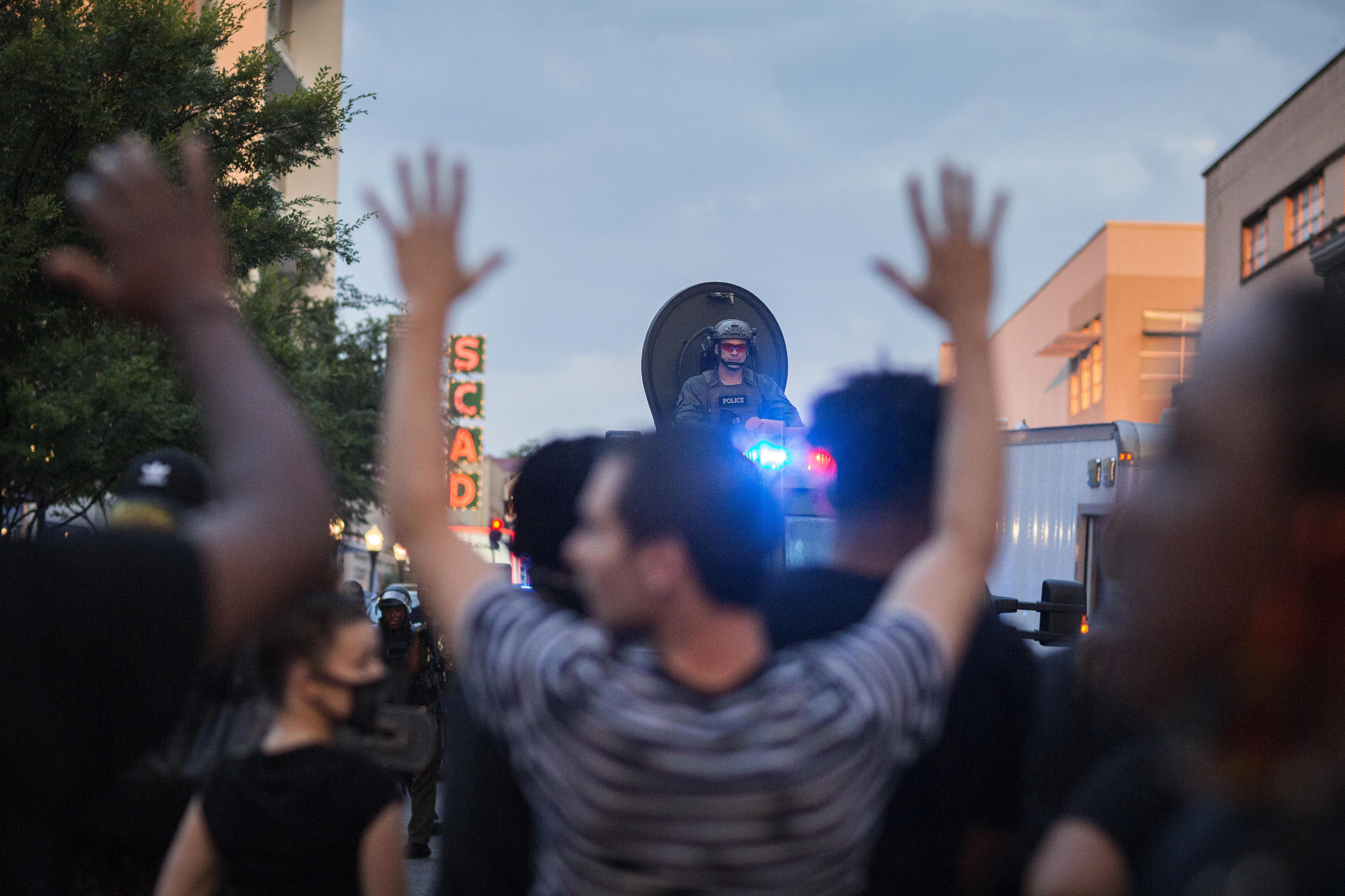 """Protesters hold hands up and chant """"don't shoot"""" during a standoff with Savannah police after a peaceful rally, Sunday, May 31, 2020, over the death of George Floyd in Minneapolis. (Stephen B. Morton/Atlanta Journal-Constitution via AP)"""