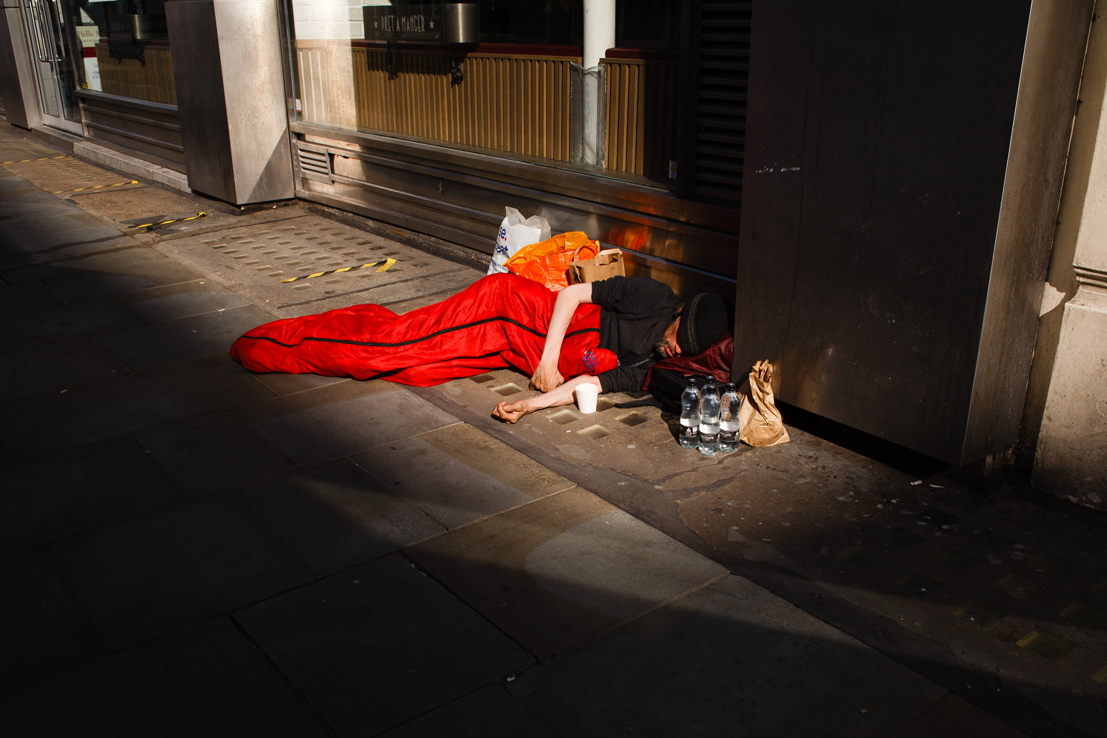 A homeless man sleeps on Cranbourn Street in London, England, on June 23, 2020. British Prime Minister Boris Johnson announced today that the next stage of lockdown easing in England would proceed on schedule, with pubs, restaurants, hotels, hairdressers, theatres, cinemas, museums, galleries, libraries, theme parks and zoos allowed to reopen from July 4. The two-metre social distancing rule is also to be halved from the same date, with people encouraged to take additional mitigation actions, such as wearing face coverings, when close together. The change, to what is being dubbed 'one-metre plus', is seen as key to the survival of the hospitality sector. (Photo by David Cliff/NurPhoto via Getty Images)