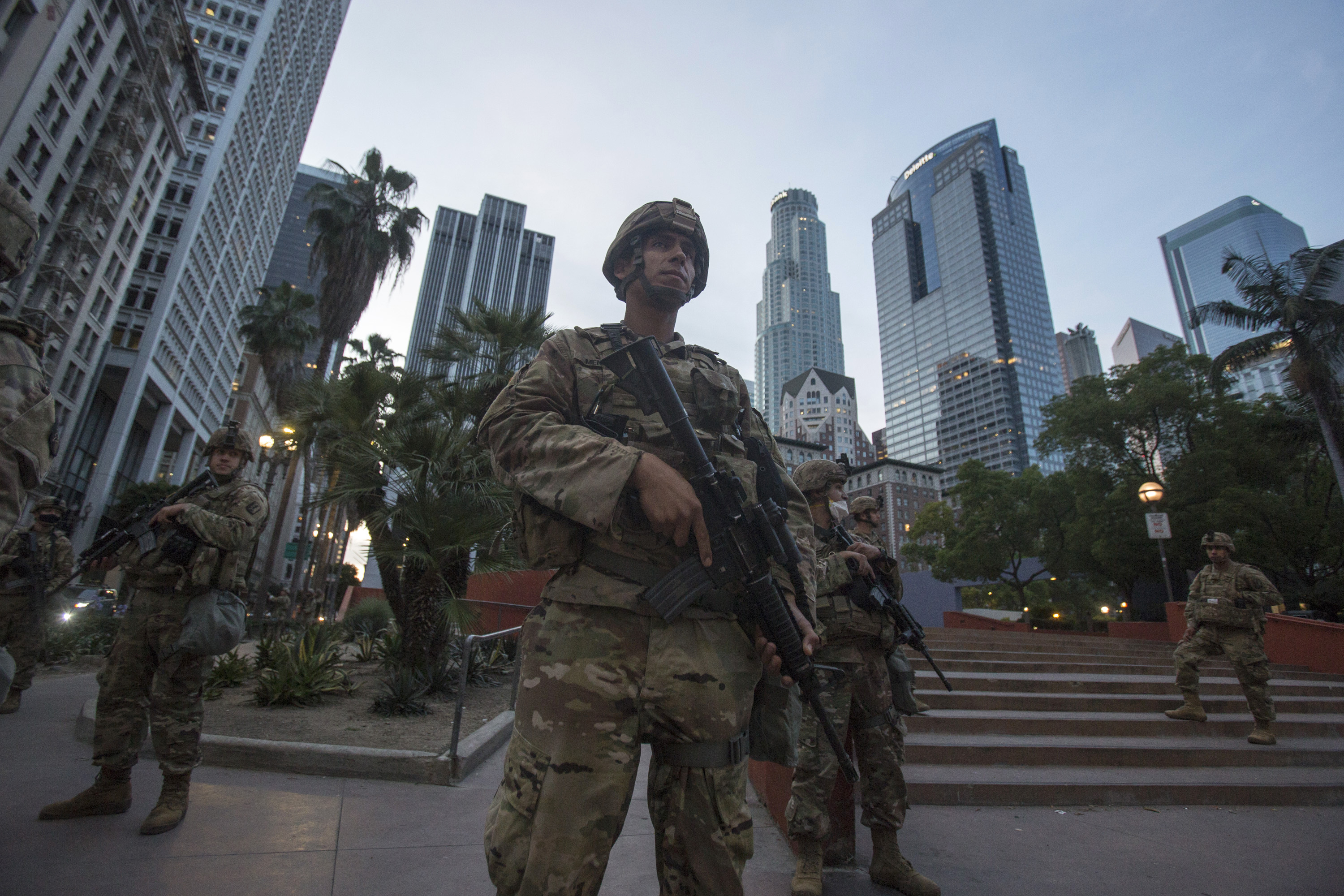 Members of California National Guard stand guard in Pershing Square, Sunday, May 31, 2020, in Los Angeles. The National Guard is patrolling Los Angeles as the city begins cleaning up after a night of violence by demonstrators that saw clash with officers and torch police vehicles and pillage stores. (AP Photo/Ringo H.W. Chiu)