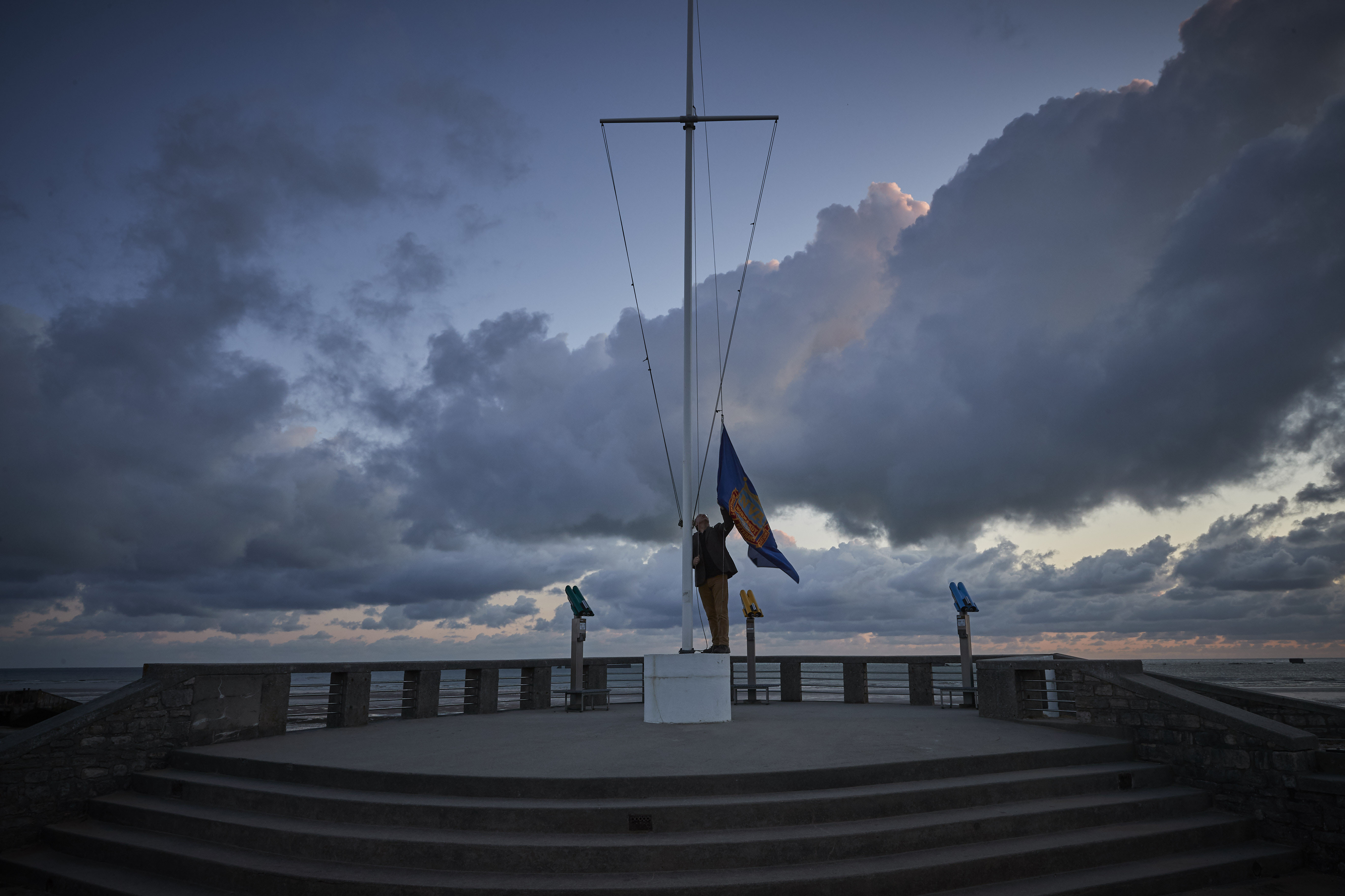 ARROMANCHES-LES-BAINS, FRANCE - JUNE 06: Adrian Cox, a British Expat and Councilor of Arromaches, raises the flag of the Normandy Veterans Association at dawn to commemorate the 76th Anniversary of the D-Day landings at dawn on Gold Beach on June 06, 2020 in Arromanches-les-Bains, France. Due to Covid-19 travel restrictions this is the first time in 75 years that veterans have not been able to attend the Anniversary.  (Photo by Kiran Ridley/Getty Images)