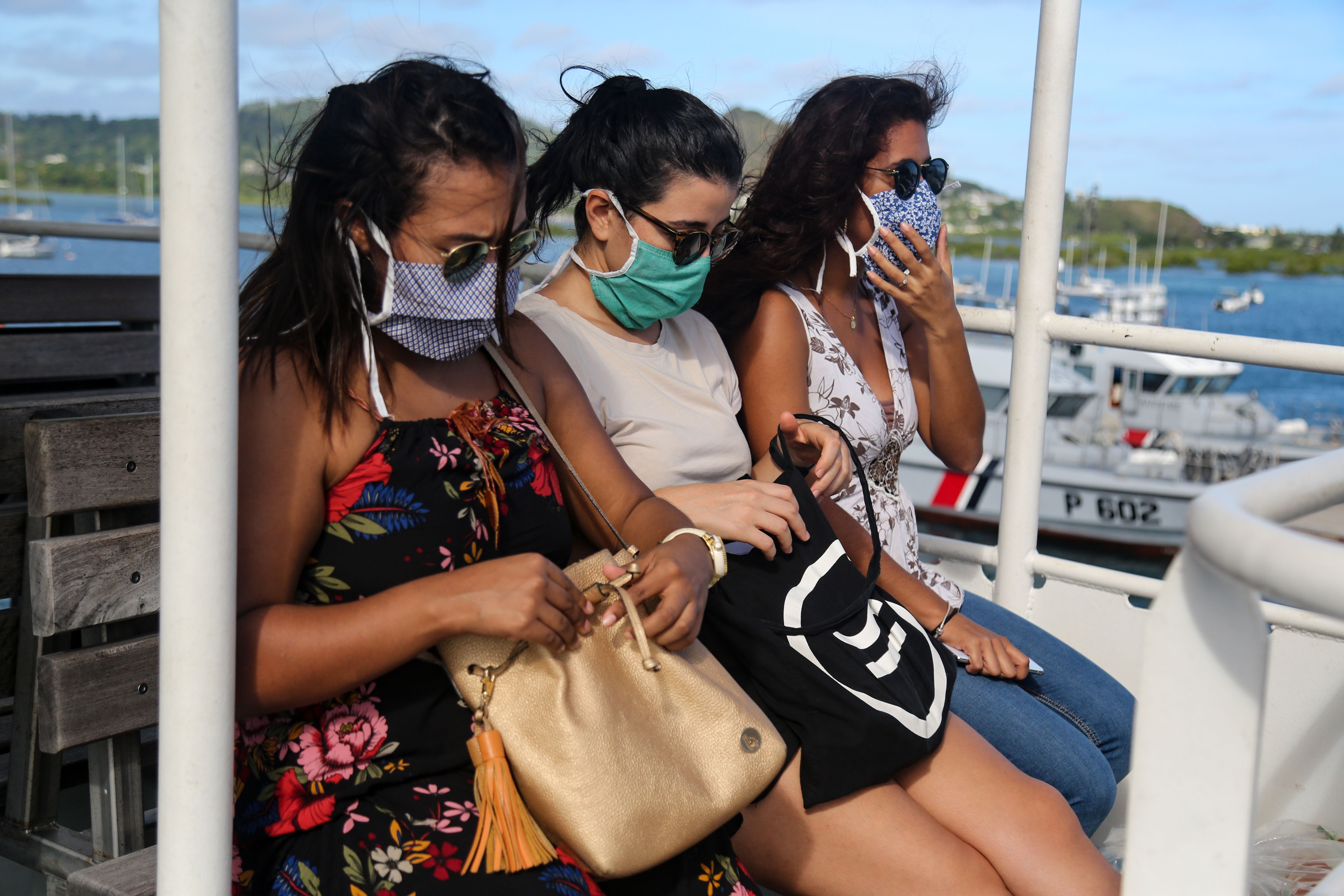 Passengers wearing protective face masks travel by boat to Petite-Terre on the French Indian Ocean island of Mayotte on June 5, 2020, as measures to curb the spread of the COVID-19 (novel coronavirus) are maintained on Mayotte over concerns about the continued spread of the virus there and a fragile health system. (Photo by Ali AL-DAHER / AFP) (Photo by ALI AL-DAHER/AFP via Getty Images)