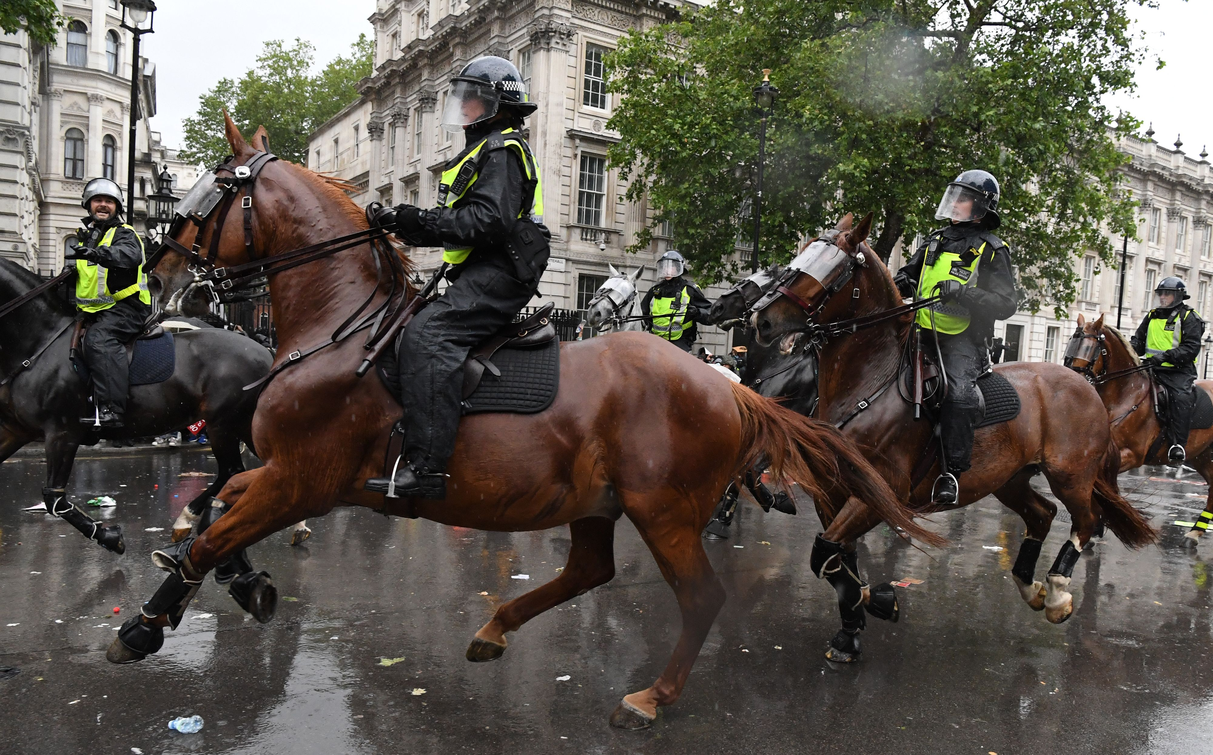 """Mounted police officers charge their horses along Whitehall, past the entrance to Downing Street, in an attempt to disperse protestors gathered in central London on June 6, 2020, during a demonstration to show solidarity with the Black Lives Matter movement in the wake of the killing of George Floyd, an unarmed black man who died after a police officer knelt on his neck in Minneapolis. - The United States braced Friday for massive weekend protests against racism and police brutality, as outrage soared over the latest law enforcement abuses against demonstrators that were caught on camera. With protests over last week's police killing of George Floyd, an unarmed black man, surging into a second weekend, President Donald Trump sparked fresh controversy by saying it was a """"great day"""" for Floyd. (Photo by DANIEL LEAL-OLIVAS / AFP) (Photo by DANIEL LEAL-OLIVAS/AFP via Getty Images)"""