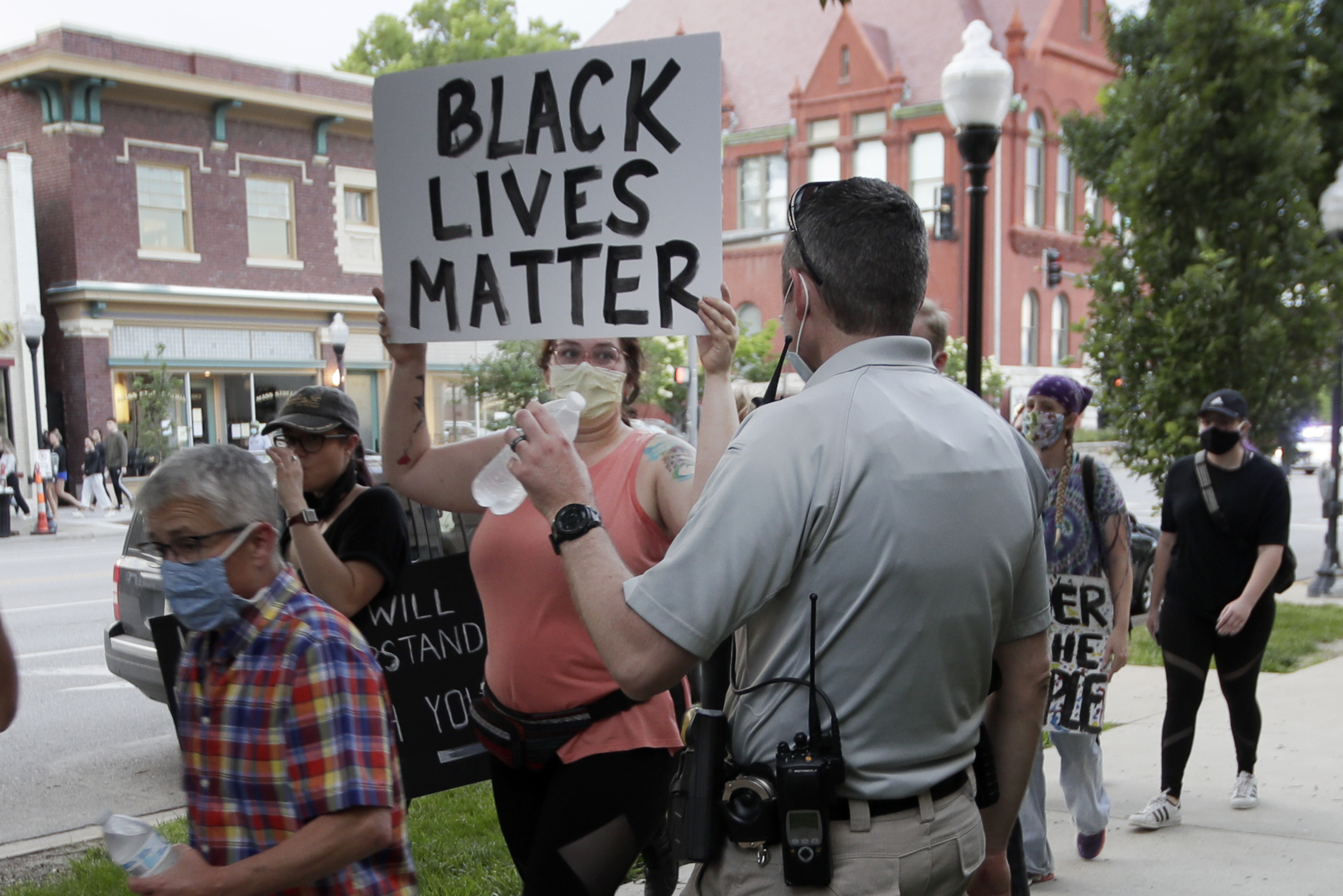 A Lawrence police officer hands water to protesters in Lawrence, Kan., Sunday, May 31, 2020, during a demonstration over the death of George Floyd, who died after being restrained by Minneapolis police officers on May 25. (AP Photo/Orlin Wagner)