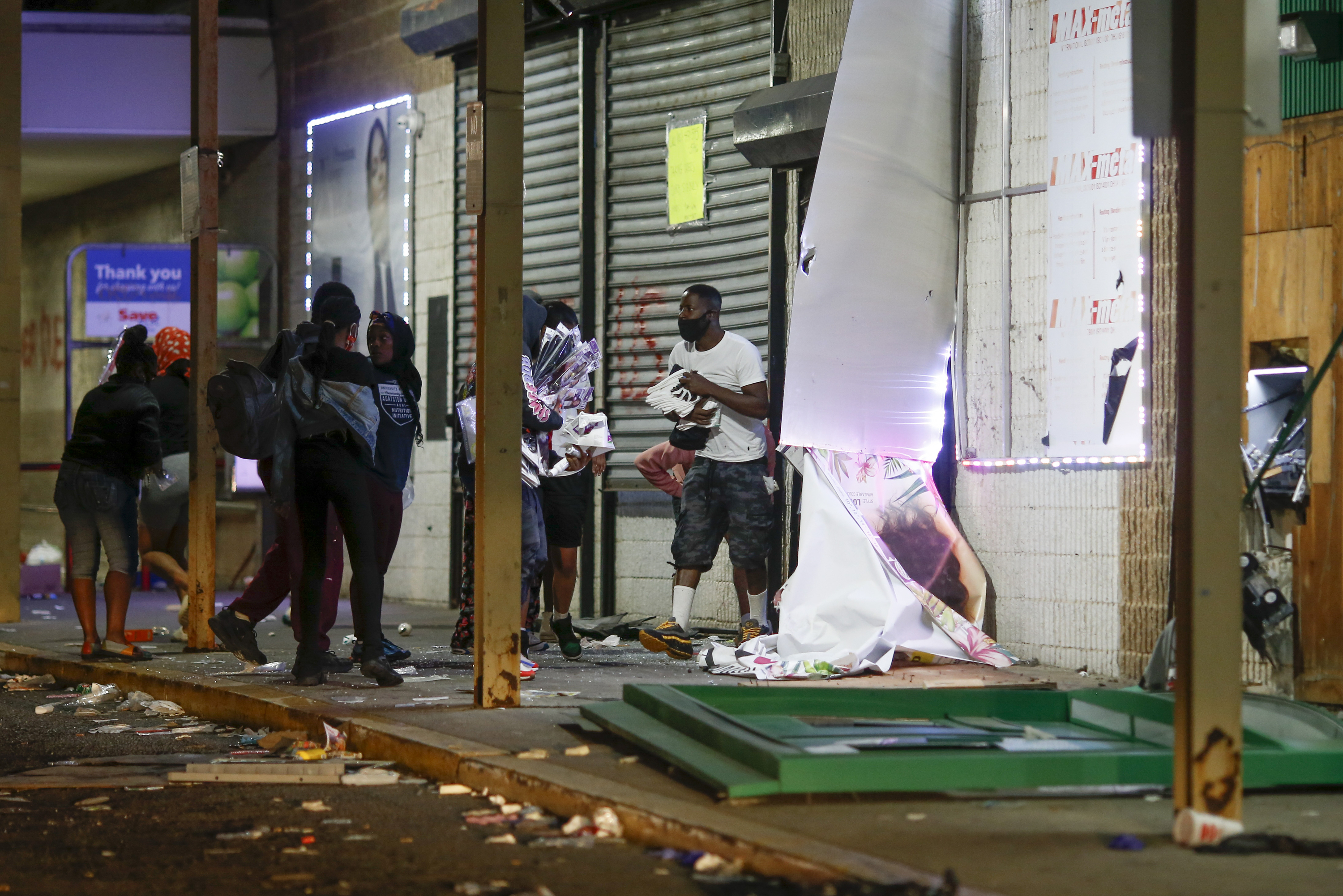 People carry packages near a security barrier on a window at a store in Philadelphia Sunday, May 31, as people protest over the death of George Floyd, a black man who was in police custody in Minneapolis. Floyd died after being restrained by Minneapolis police officers on Memorial Day, May 25. (AP Photo/Matt Slocum)