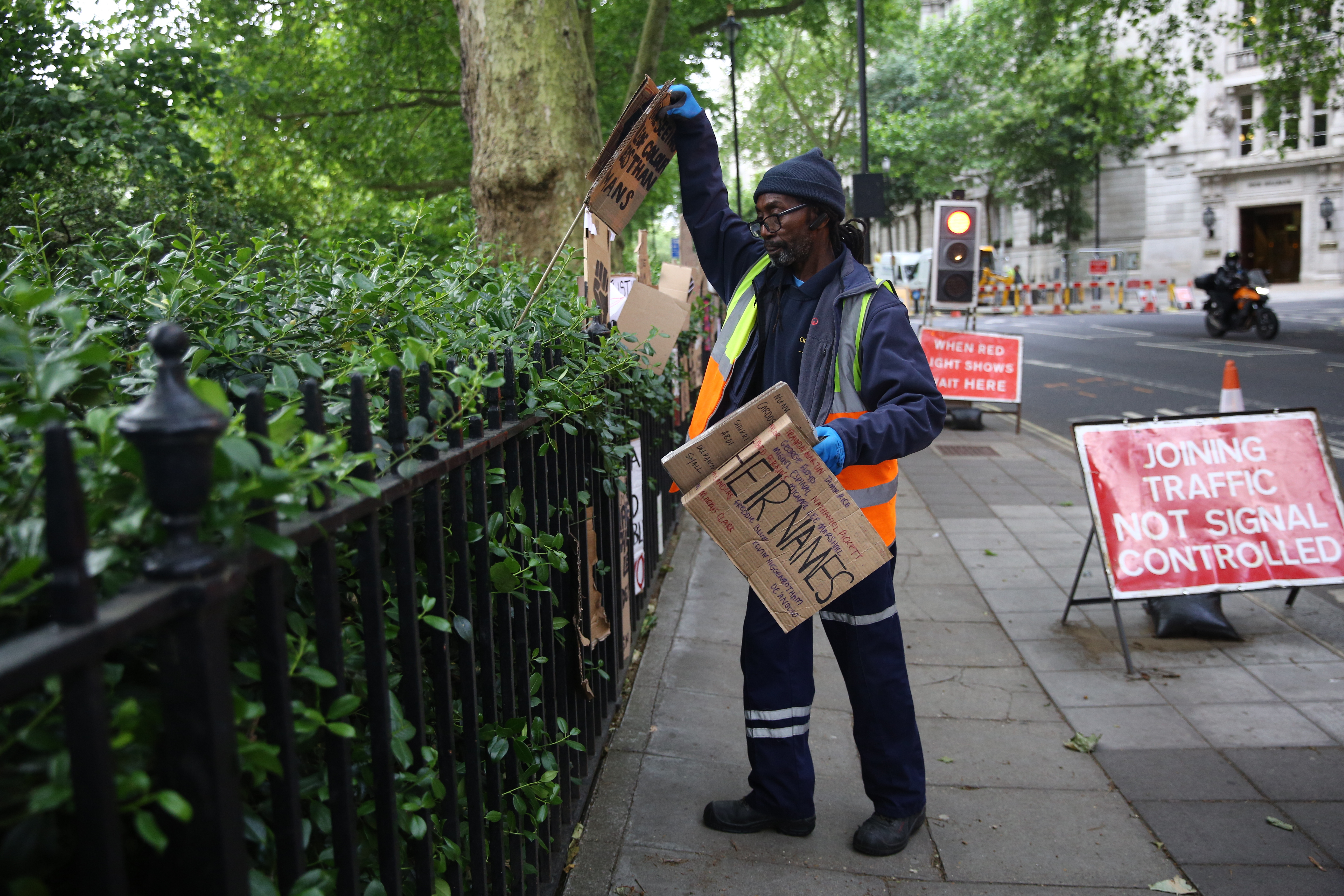 A worker collects discarded placards from Victoria Tower Gardens in Westminster, London, following a Black Lives Matter protest at the weekend. A raft of protests across the UK were sparked by the death of George Floyd, who was killed on May 25 while in police custody in the US city of Minneapolis.