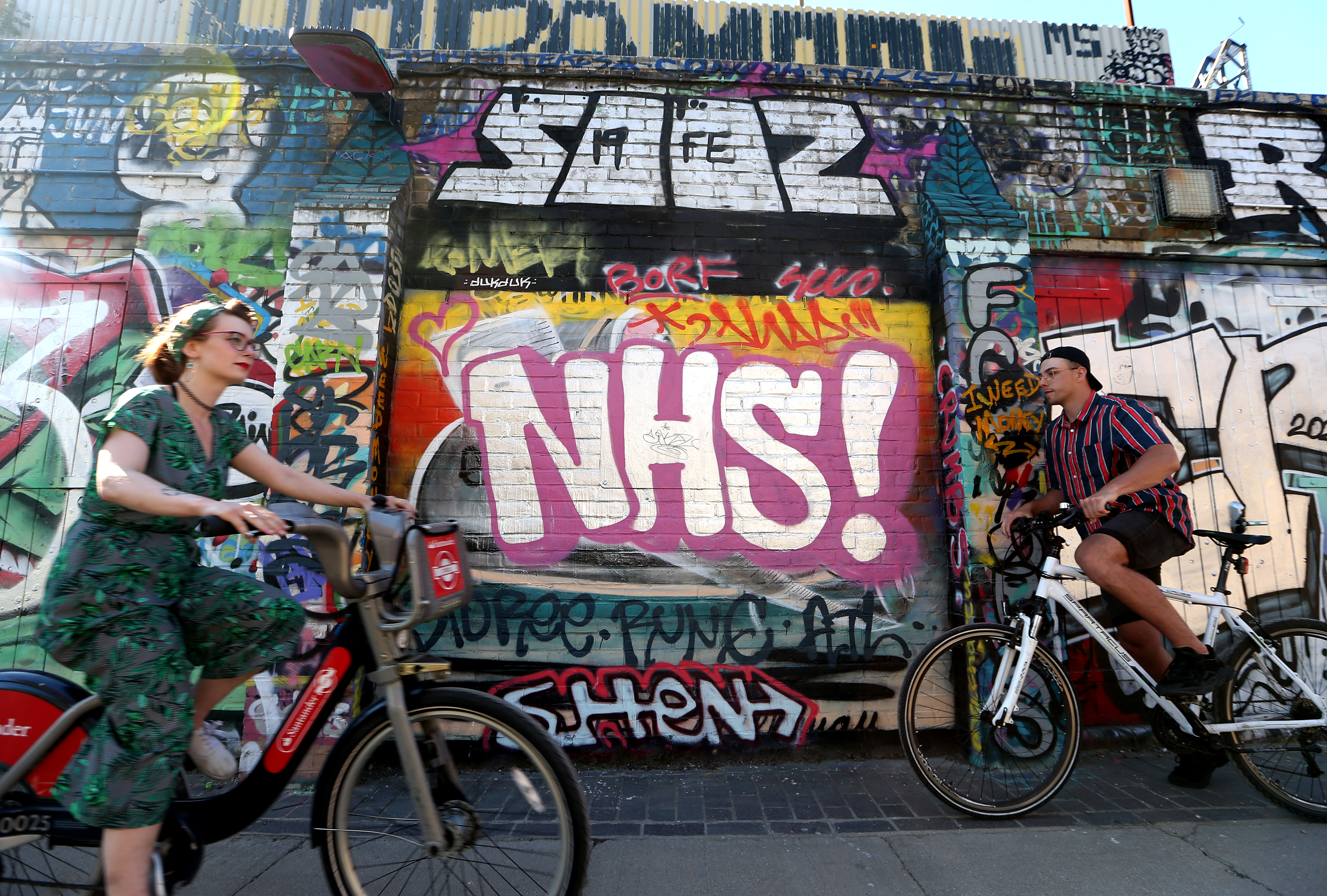 LONDON, ENGLAND  - MAY 31: Cyclists pass graffiti reading 'NHS'  in Hackney Wick on May 31, 2020 in London, England. The British government continues to ease the coronavirus lockdown by announcing schools will open to reception year pupils plus years one and six from June 1st. Open-air markets and car showrooms can also open from the same date.  (Photo by Alex Pantling/Getty Images)