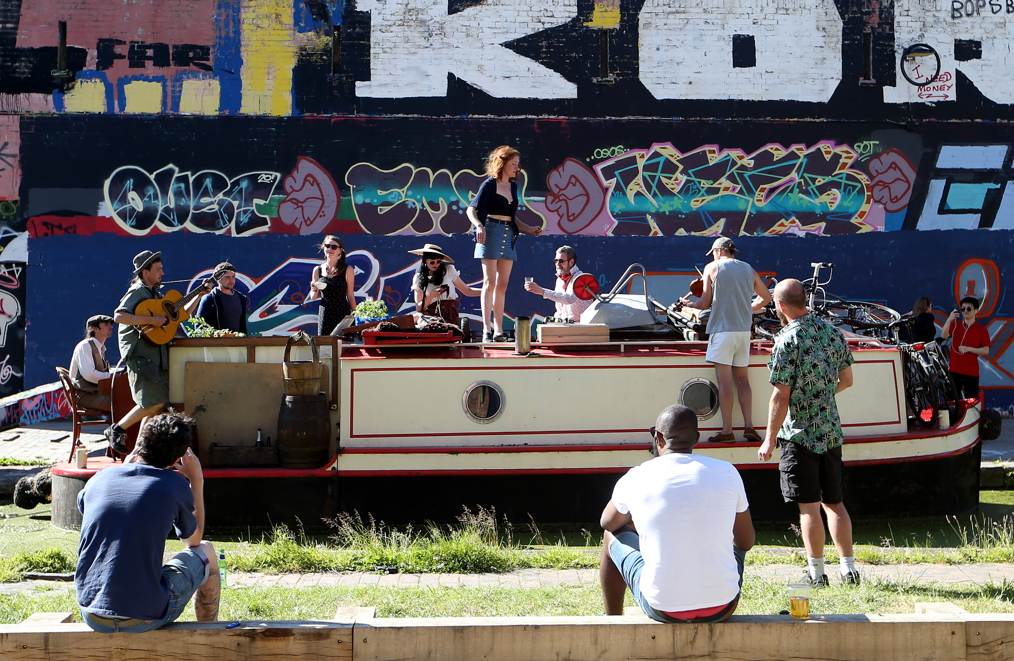 LONDON, ENGLAND  - MAY 31: A band play musical instruments on a canal boat in Hackney Wick on May 31, 2020 in London, England. The British government continues to ease the coronavirus lockdown by announcing schools will open to reception year pupils plus years one and six from June 1st. Open-air markets and car showrooms can also open from the same date.  (Photo by Alex Pantling/Getty Images)