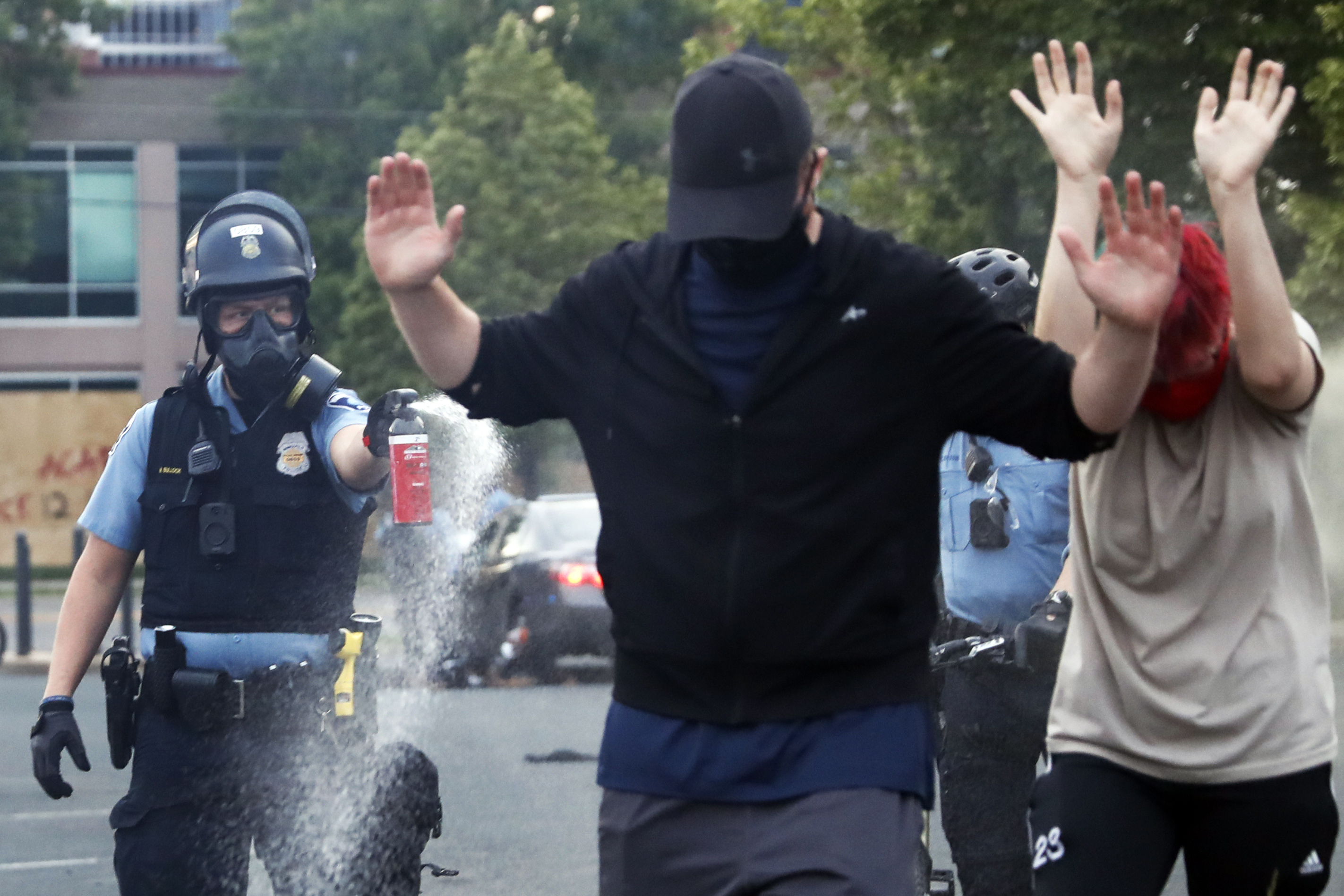 An officer points pepper spray towards people after curfew on Sunday, May 31, 2020 in Minneapolis. Protests continued following the death of George Floyd, who died after being restrained by Minneapolis police officers on Memorial Day. (AP Photo/John Minchillo)