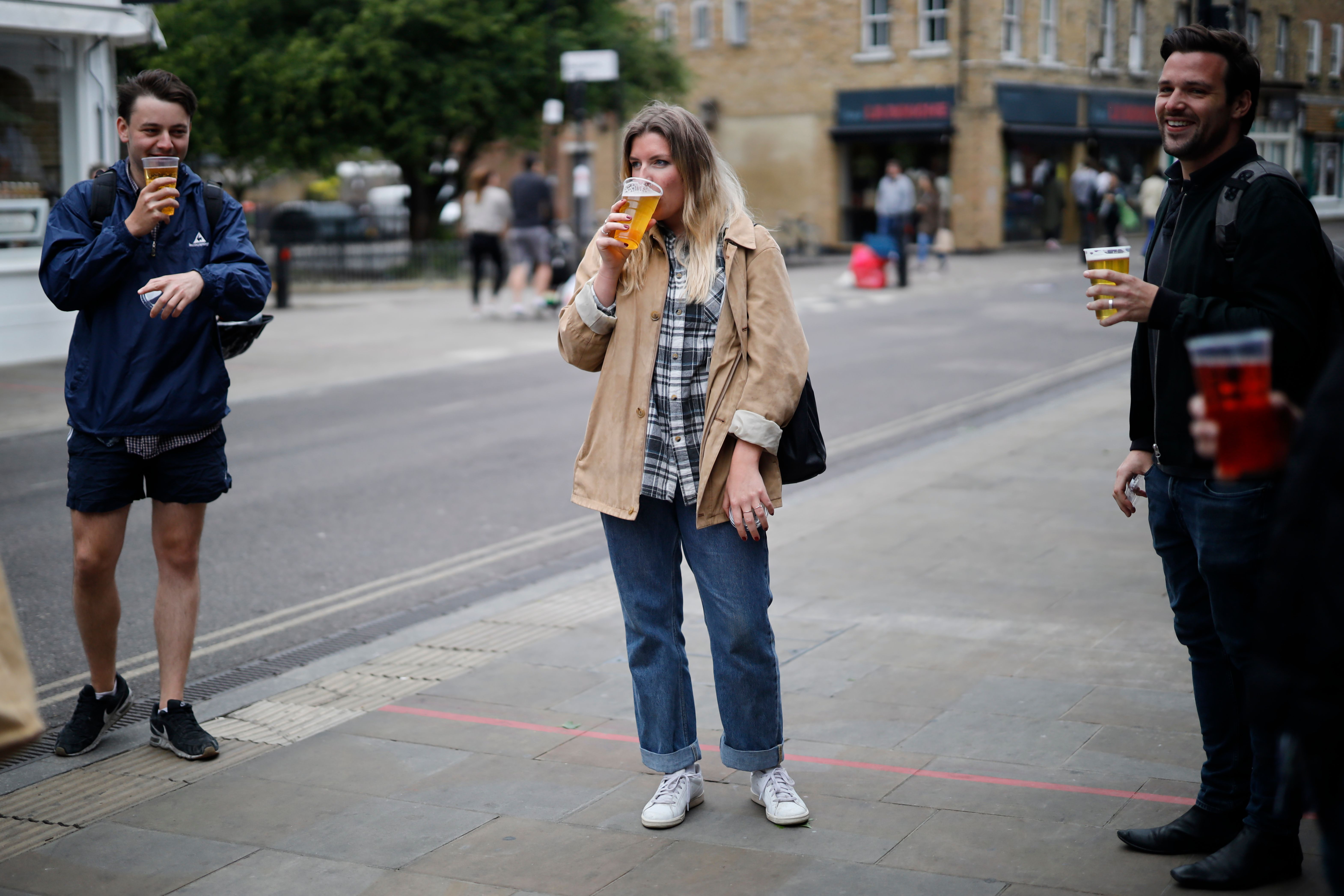 Customers chat as they drink their takeaway draught beer in plastic cups outside a pub in Broadway Market, London on June  5, 2020, as lockdown measures are eased during the novel coronavirus COVID-19 pandemic. (Photo by Tolga Akmen / AFP) (Photo by TOLGA AKMEN/AFP via Getty Images)