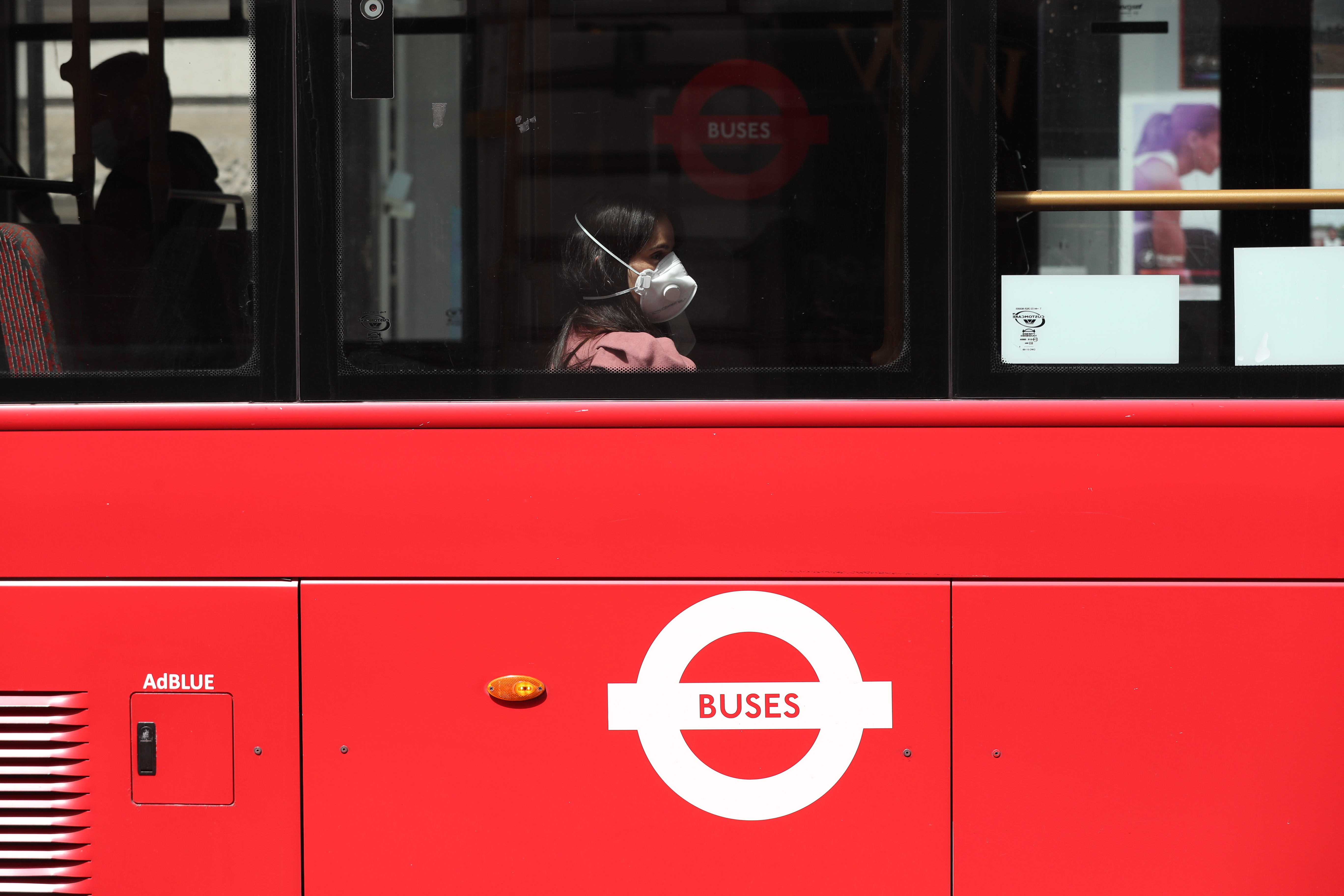 A person wearing a face mask rides a bus on Piccadilly, London, following the introduction of measures to bring England out of lockdown. (Photo by Jonathan Brady/PA Images via Getty Images)
