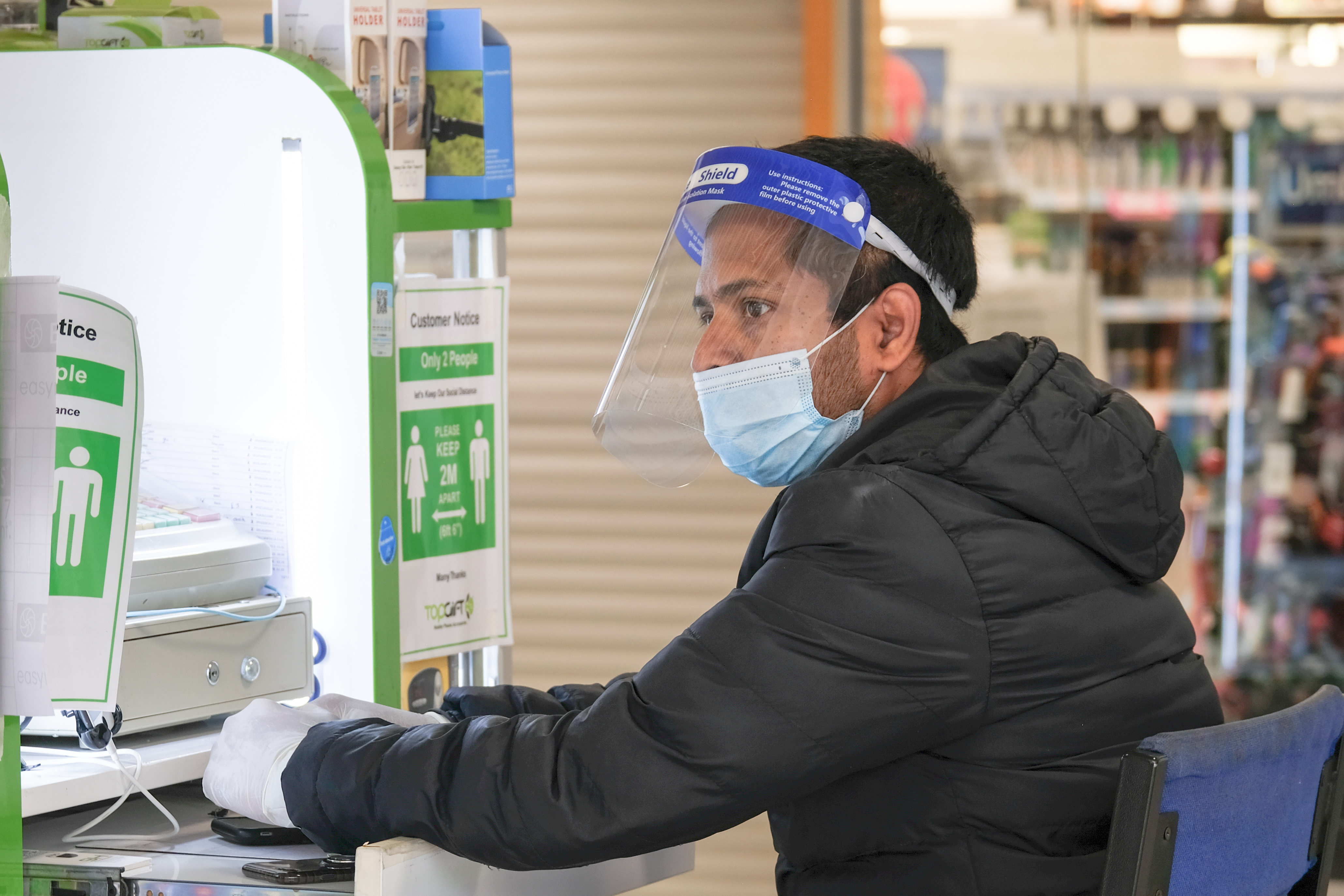 An employee at Top Gift Mobile stall wears a face shield and mask as preventive measure while working. (Photo by Dawn Fletcher-Park / SOPA Images/Sipa USA)