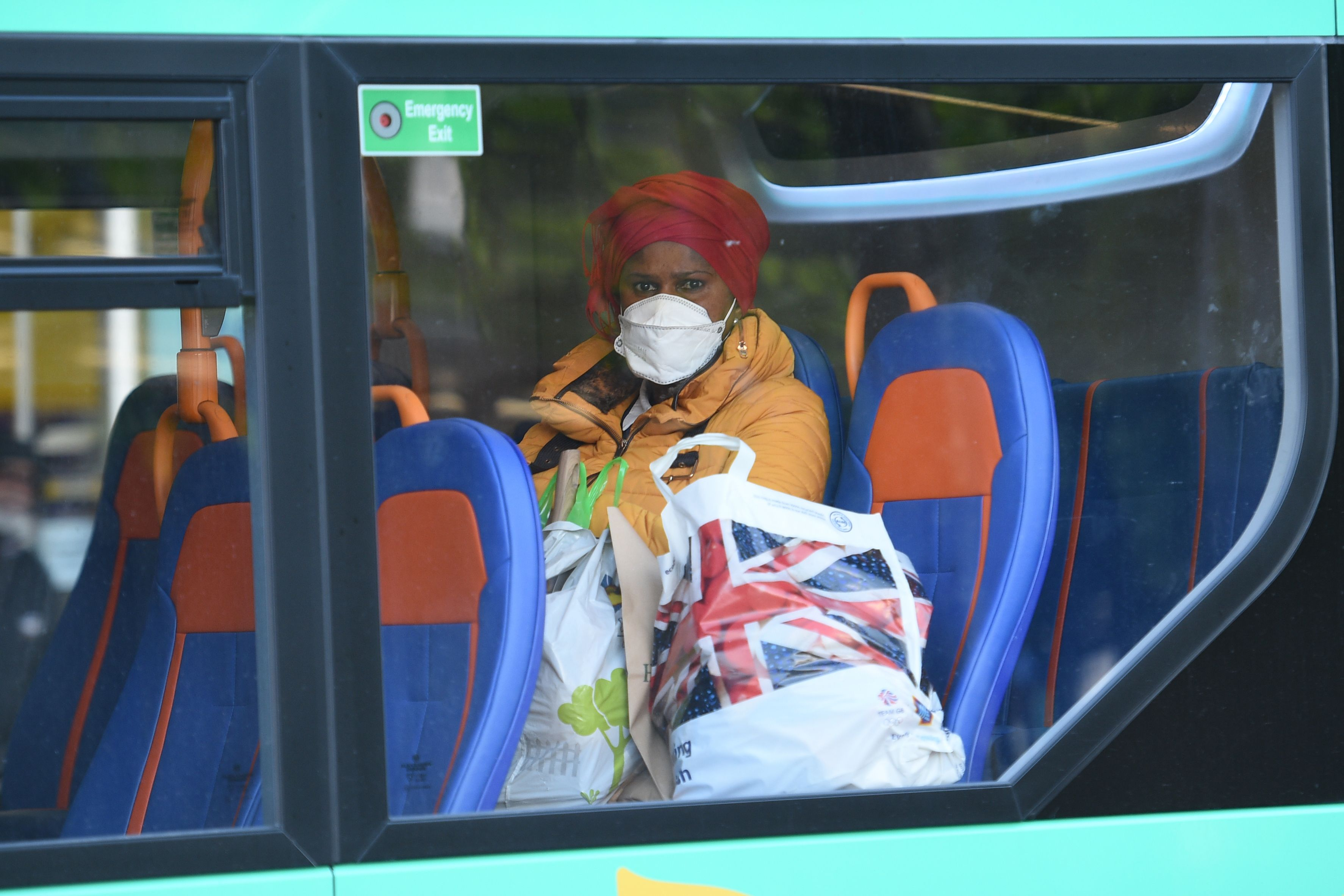 A woman wears a protective face mask on a bus in central Manchester on June 5, 2020, as lockdown measures are eased during the novel coronavirus COVID-19 pandemic. - Face coverings will soon be compulsory for people wanting to travel on public transport in England to limit the spread of coronavirus. (Photo by Oli SCARFF / AFP) (Photo by OLI SCARFF/AFP via Getty Images)
