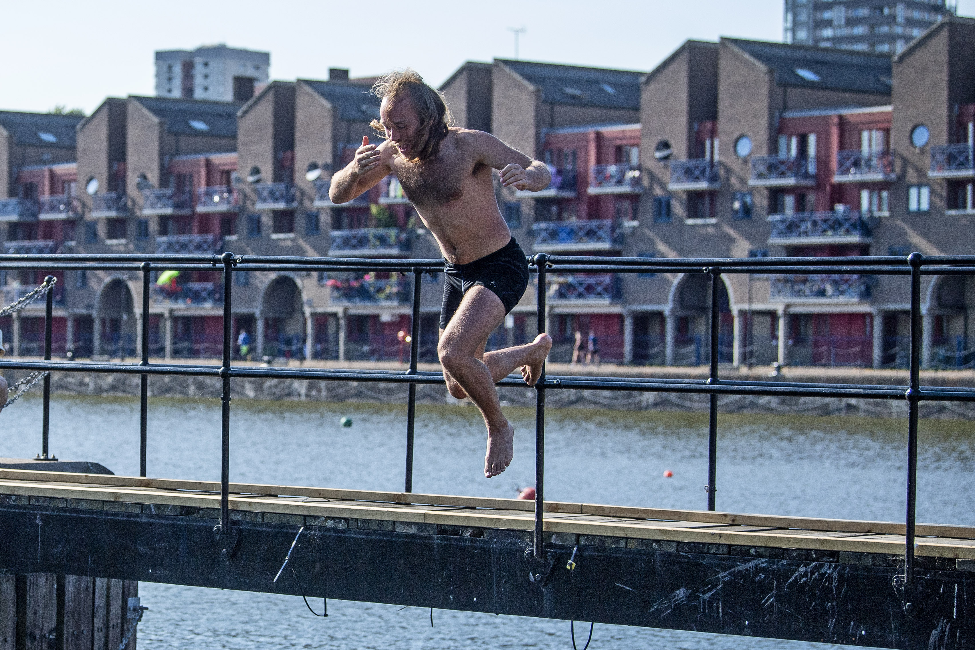 A man jumps into a disused dock in East London as Thursday could be the UK's hottest day of the year with scorching temperatures forecast to rise even further.