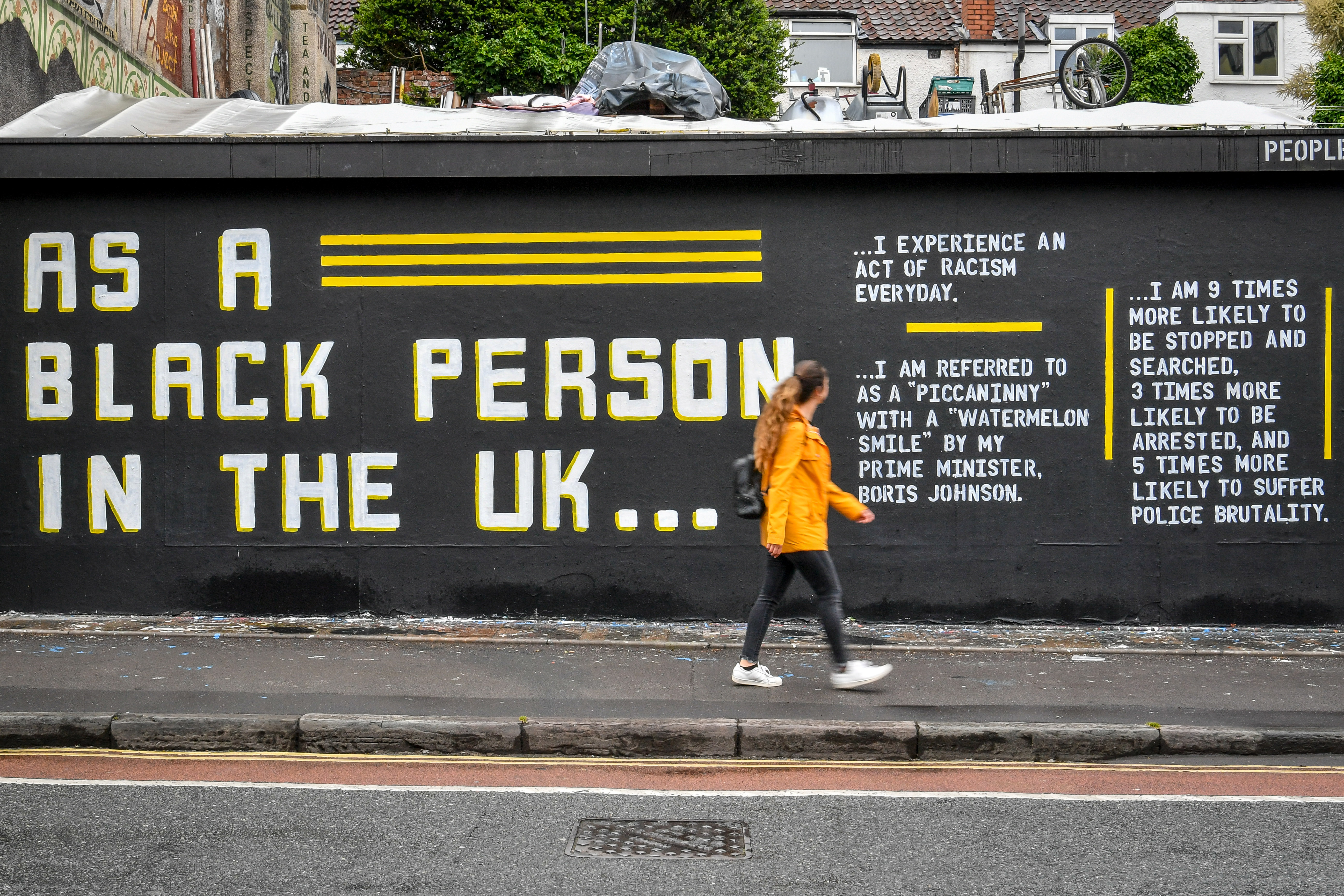 A woman looks at a graffiti art piece on Black Lives Matter on a wall in the Stokes Croft area of Bristol following a raft of Black Lives Matter protests took place across the UK over the weekend. The protests were sparked by the death of George Floyd, who was killed on May 25 while in police custody in the US city of Minneapolis.