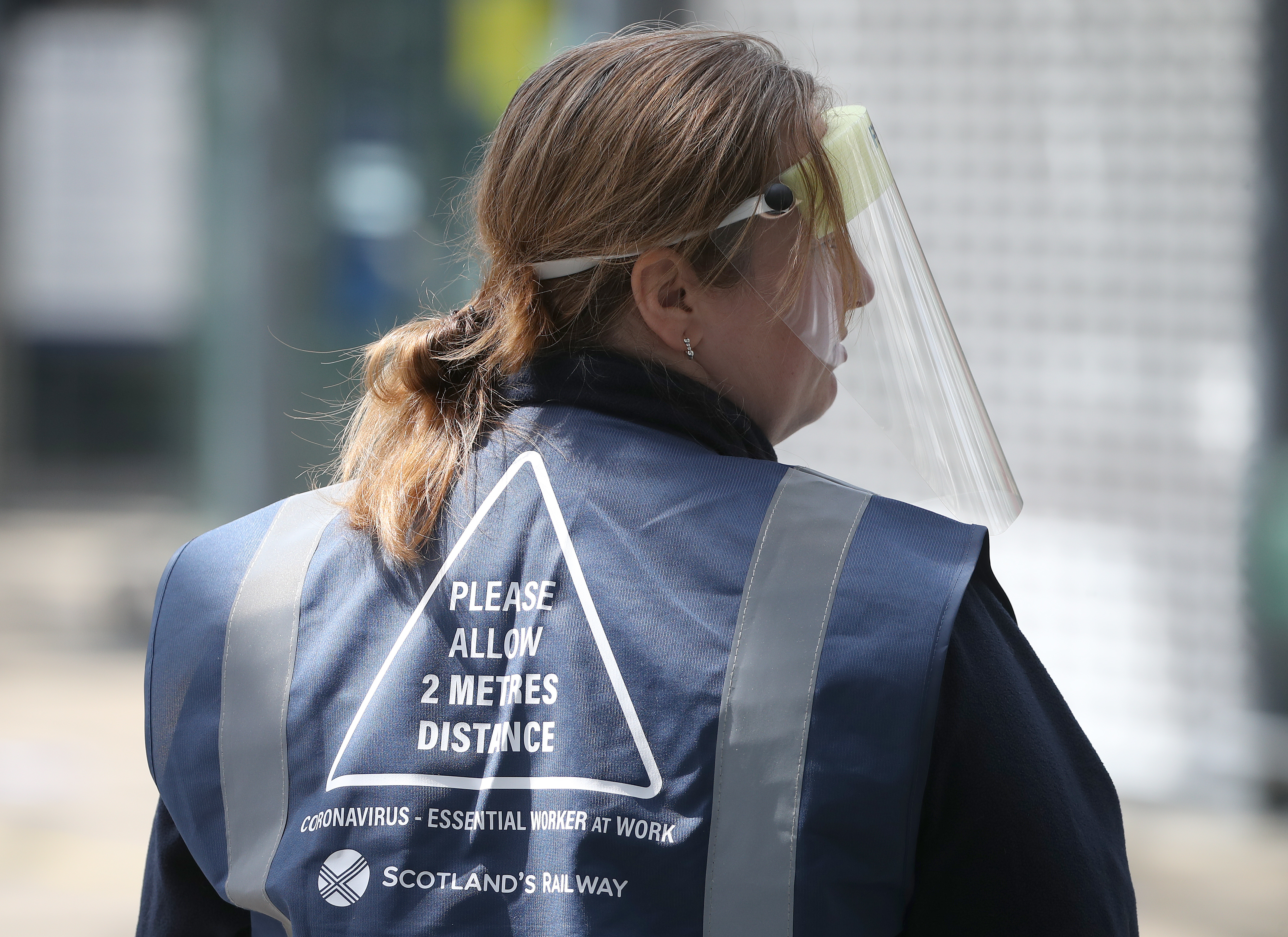 A person wears a jacket with Social distance guidelines printed on it at Edinburgh Waverley Station as Scotland moves into phase one of the Scottish Government's plan for gradually lifting lockdown. (Photo by Andrew Milligan/PA Images via Getty Images)