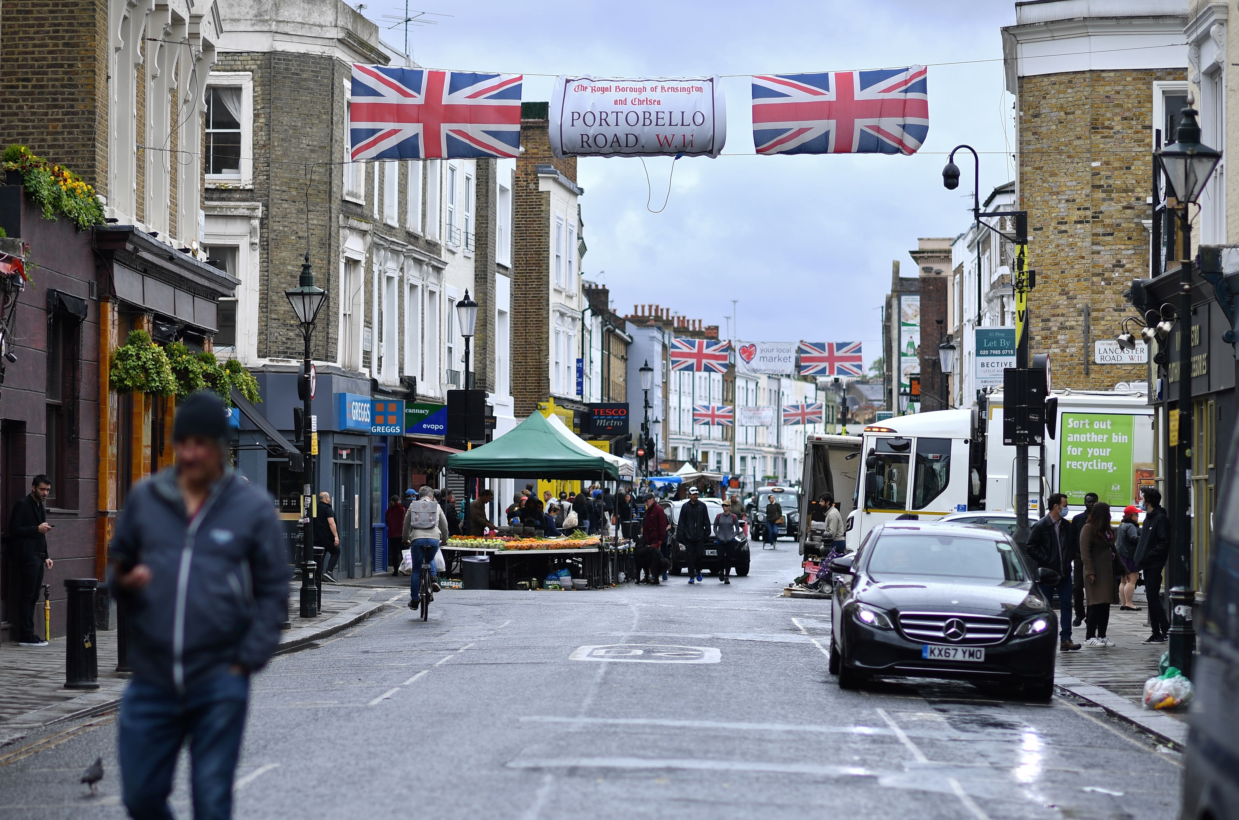 People walk past stalls at an almost deserted Portobello Road Market in London on June 6, 2020, as lockdown measures are partially eased during the novel coronavirus COVID-19 pandemic. - Outdoor markets swung open their gates on June 1, and car showrooms tried to lure back customers and recoup losses suffered since Britain effectively shut down for business on March 23, to ward off a disease that has now officially claimed more than 40,000 lives in the country. Britain's Health Ministry said 40,261 people who tested positive for COVID-19 had died as of 0800 GMT on Friday June 5. (Photo by Ben STANSALL / AFP) (Photo by BEN STANSALL/AFP via Getty Images)