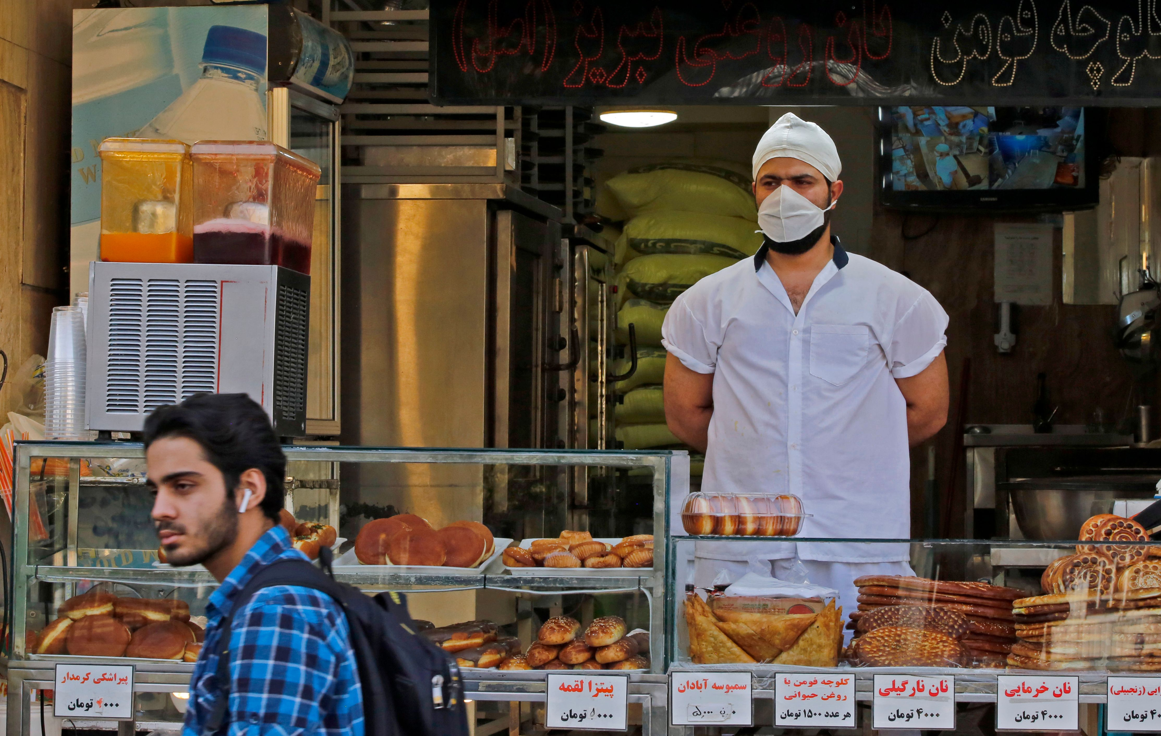An Iranian man walks in front of a pstry shop in the capital Tehran on June 3, 2020, amid the novel coronavirus pandemic crisis. - The spread of novel coronavirus has accelerated again this month in Iran which today officially confirmed over 3,000 new cases for a third consecutive day. (Photo by - / AFP) (Photo by -/afp/AFP via Getty Images)