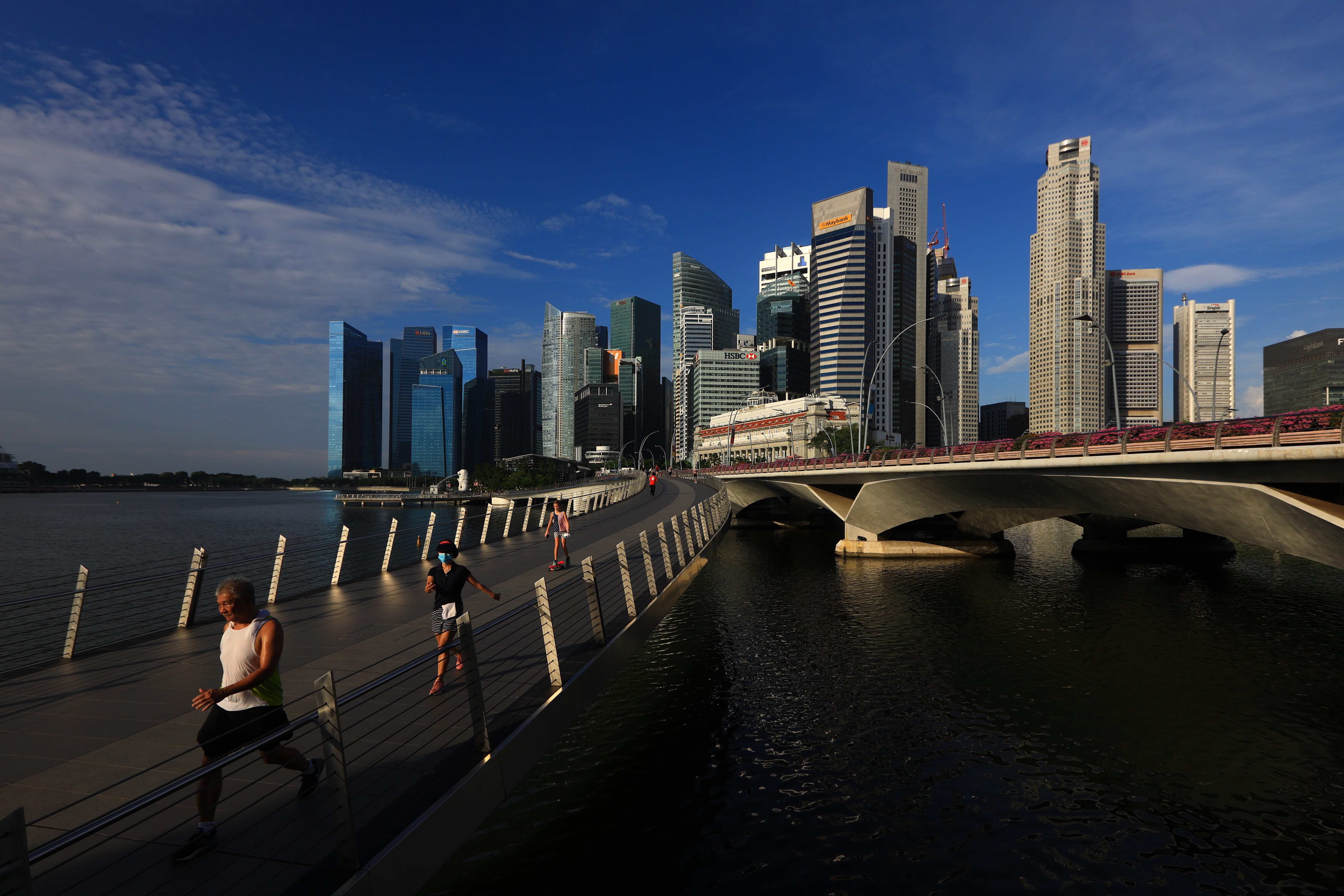 SINGAPORE - JUNE 07:  People jog along the Jubilee Bridge with the central business district seen in the background on June 7, 2020 in Singapore. From June 2, Singapore embarked on phase one of a three phase approach against the coronavirus (COVID-19) pandemic as it began to ease the partial lockdown measures by allowing the safe re-opening of economic activities which do not pose high risk of transmission. This include the resumption of selected health services, re-opening of schools with school children attending schools on rotational basis, manufacturing and production facilities, construction sites that adhere to safety measures, finance and information services that do not require interactions and places of worship, amongst others. Retail outlets, social and entertainment activities will remain closed and dining in at food and beverage outlets will still be disallowed. The government will further ease restriction by the middle of June if the infection rate within the community remains low over the next two weeks.  (Photo by Suhaimi Abdullah/Getty Images)