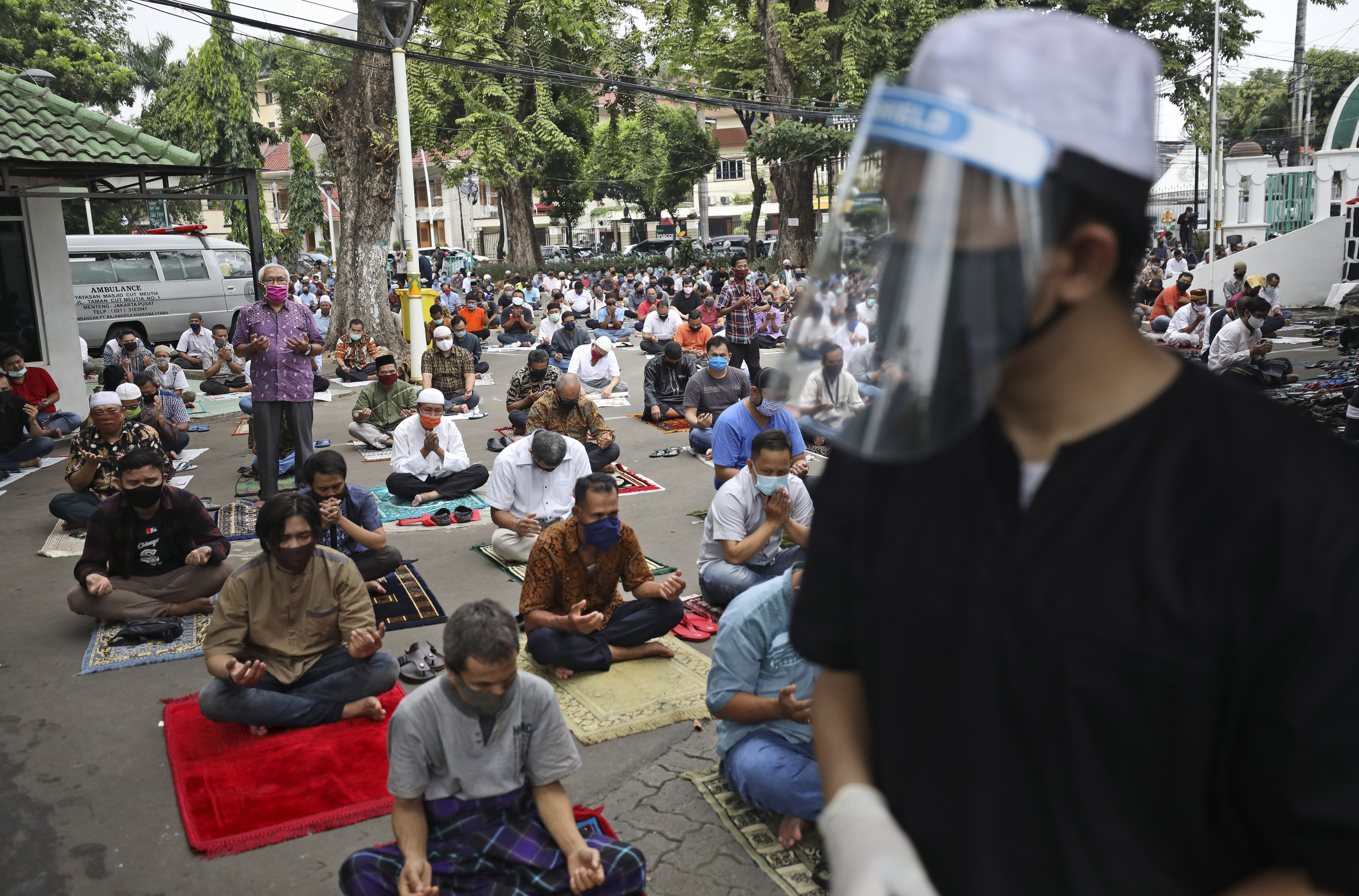 A mosque official in protective gear tasked to take the temperature readings of arriving worshippers, waits at the gate of the Cut Meutia Mosque during a Friday prayer in Jakarta, Indonesia, Friday, June 5, 2020. Muslims in Indonesia's capital held their first communal Friday prayers as mosques closed by the coronavirus outbreak for nine weeks reopened at half capacity. (AP Photo/Dita Alangkara)