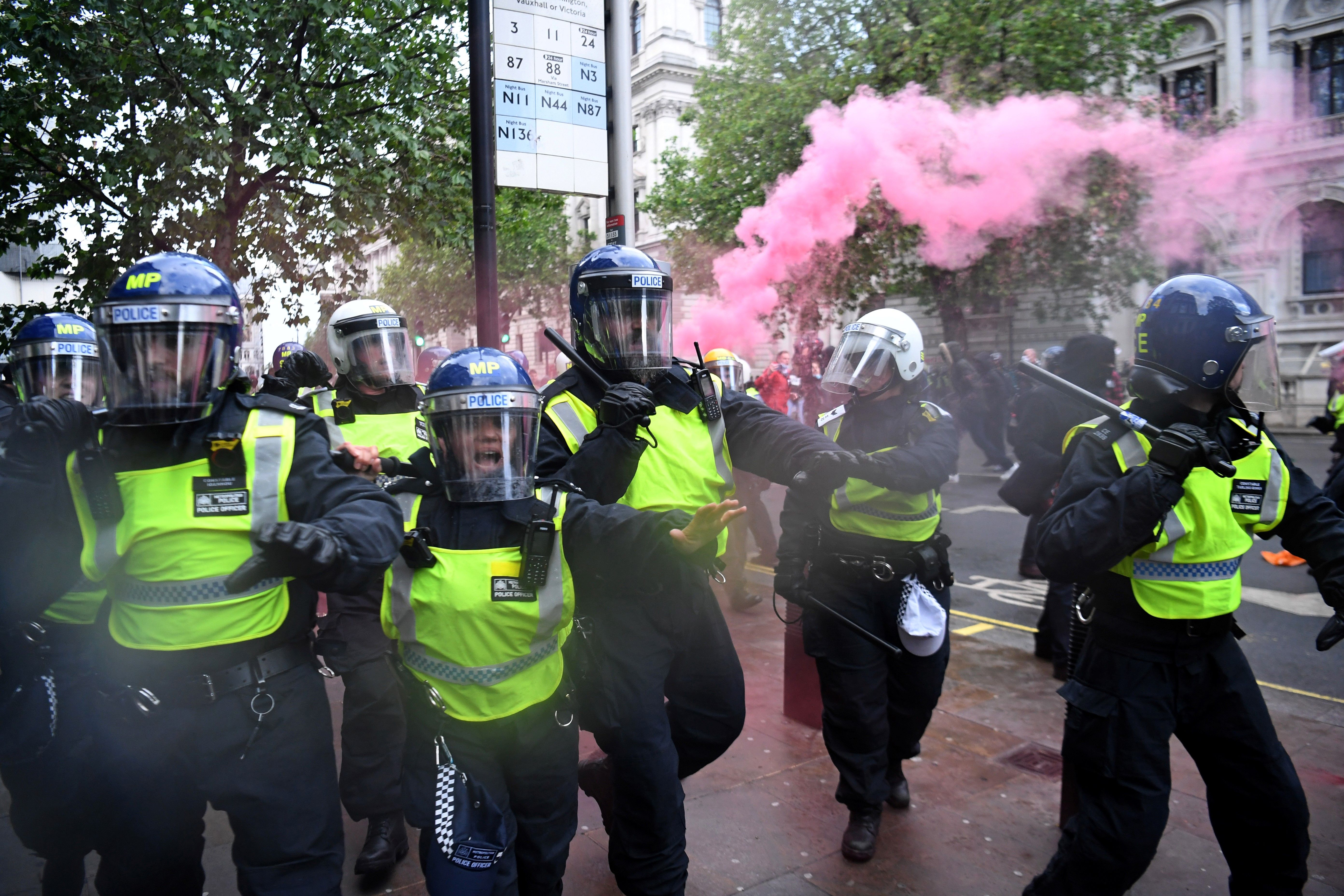 """Police officers in riot gear shout to protestors near Downing Street, in central London on June 6, 2020, during a demonstration organised to show solidarity with the Black Lives Matter movement in the wake of the killing of George Floyd, an unarmed black man who died after a police officer knelt on his neck in Minneapolis. - The United States braced Friday for massive weekend protests against racism and police brutality, as outrage soared over the latest law enforcement abuses against demonstrators that were caught on camera. With protests over last week's police killing of George Floyd, an unarmed black man, surging into a second weekend, President Donald Trump sparked fresh controversy by saying it was a """"great day"""" for Floyd. (Photo by DANIEL LEAL-OLIVAS / AFP) (Photo by DANIEL LEAL-OLIVAS/AFP via Getty Images)"""