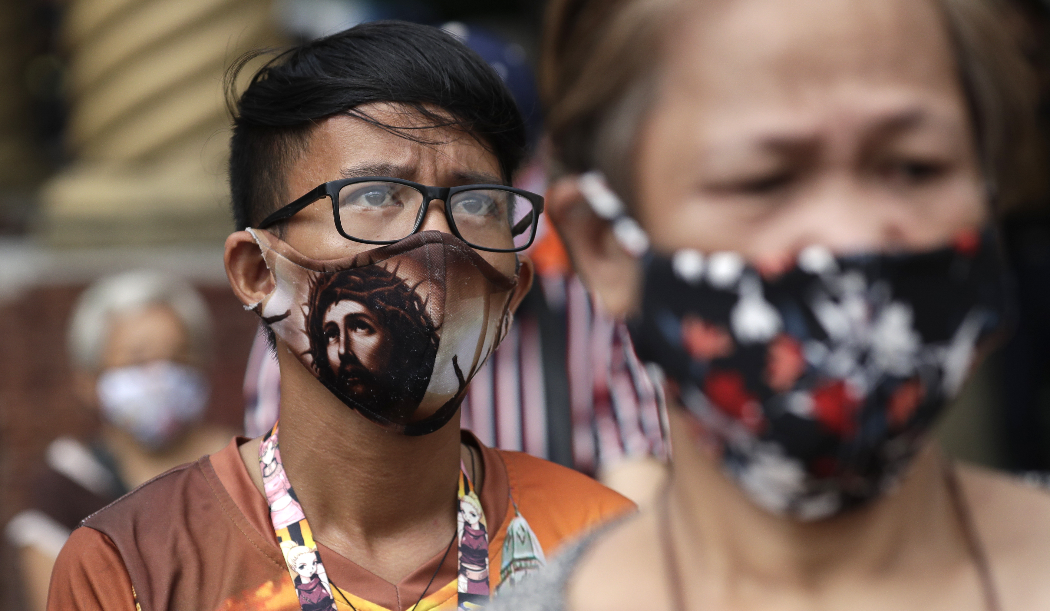 """A devotee wearing a protective mask bearing the face of Jesus Christ waits outside the Minor Basilica of the Black Nazarene, popularly known as Quiapo church, as it slowly reopens its doors in downtown Manila, Philippines on Friday, June 5, 2020. President Rodrigo Duterte has expressed relief that """"Filipinos are really law-abiding"""" and that the Philippines was not going through riots like America which would make coronavirus quarantine enforcement formidable. (AP Photo/Aaron Favila)"""