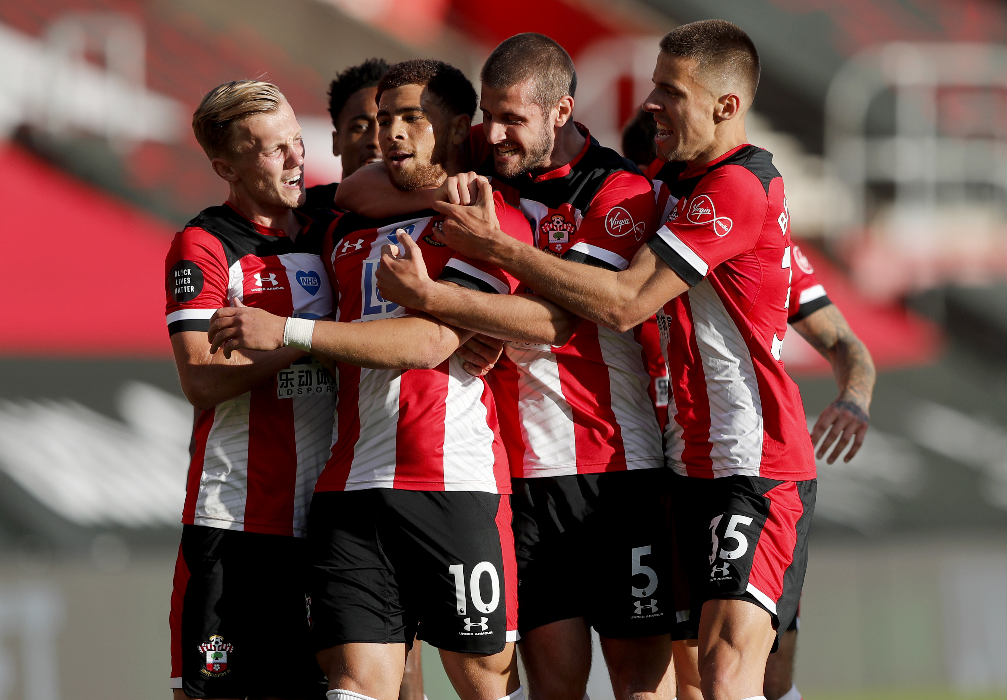Southampton's Che Adams, second left, is congratulated by teammates after scoring his team's first goal during the English Premier League soccer match between Southampton and Manchester City at St. Mary's Stadium in Southampton, England, Sunday, July 5, 2020. (AP Photo/Frank Augstein,Pool)