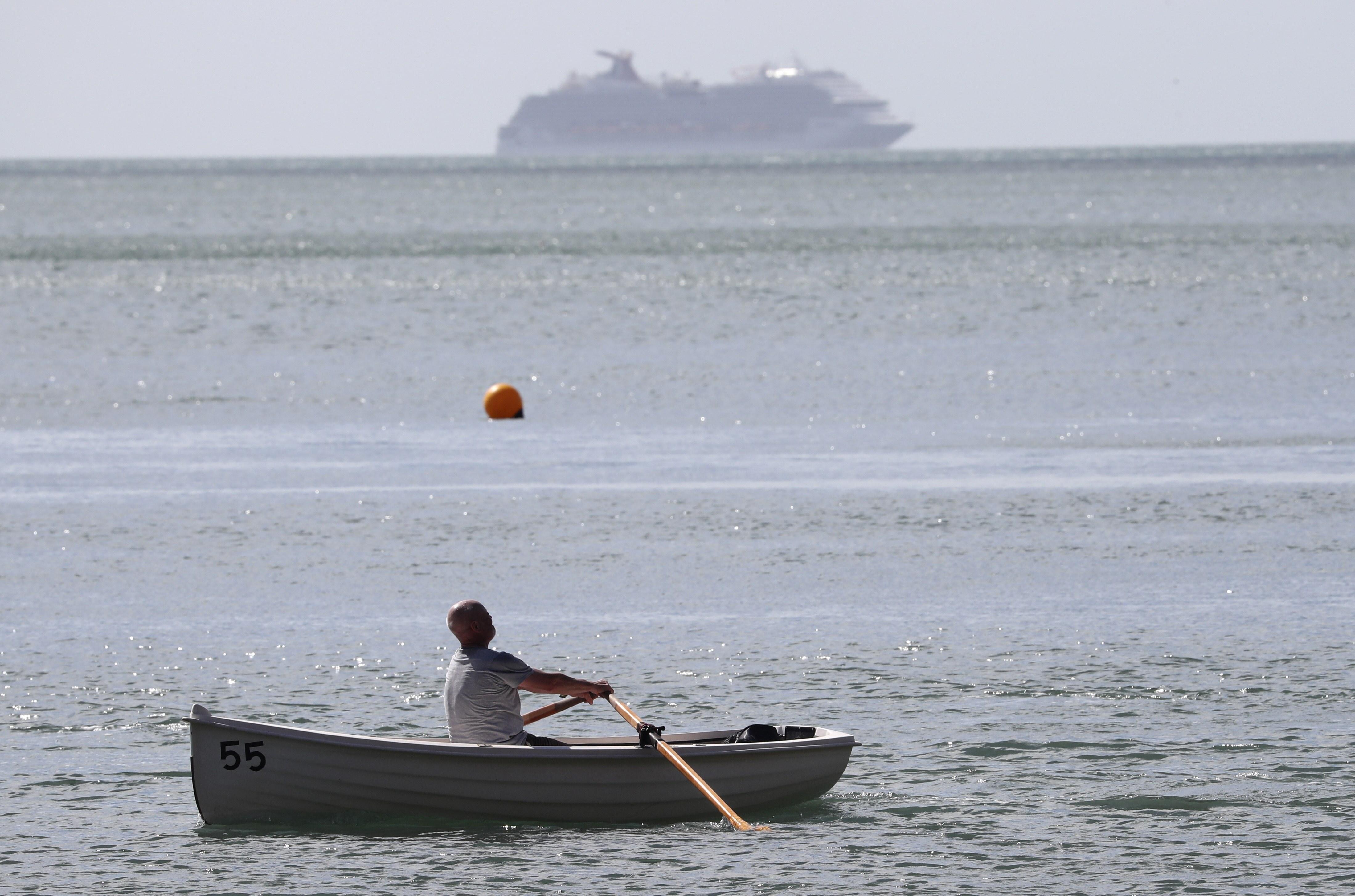 A man rows a boat across Ness Cove in Shaldon, England, Sunday, July 5, 2020. (AP photo/Tony Hicks)