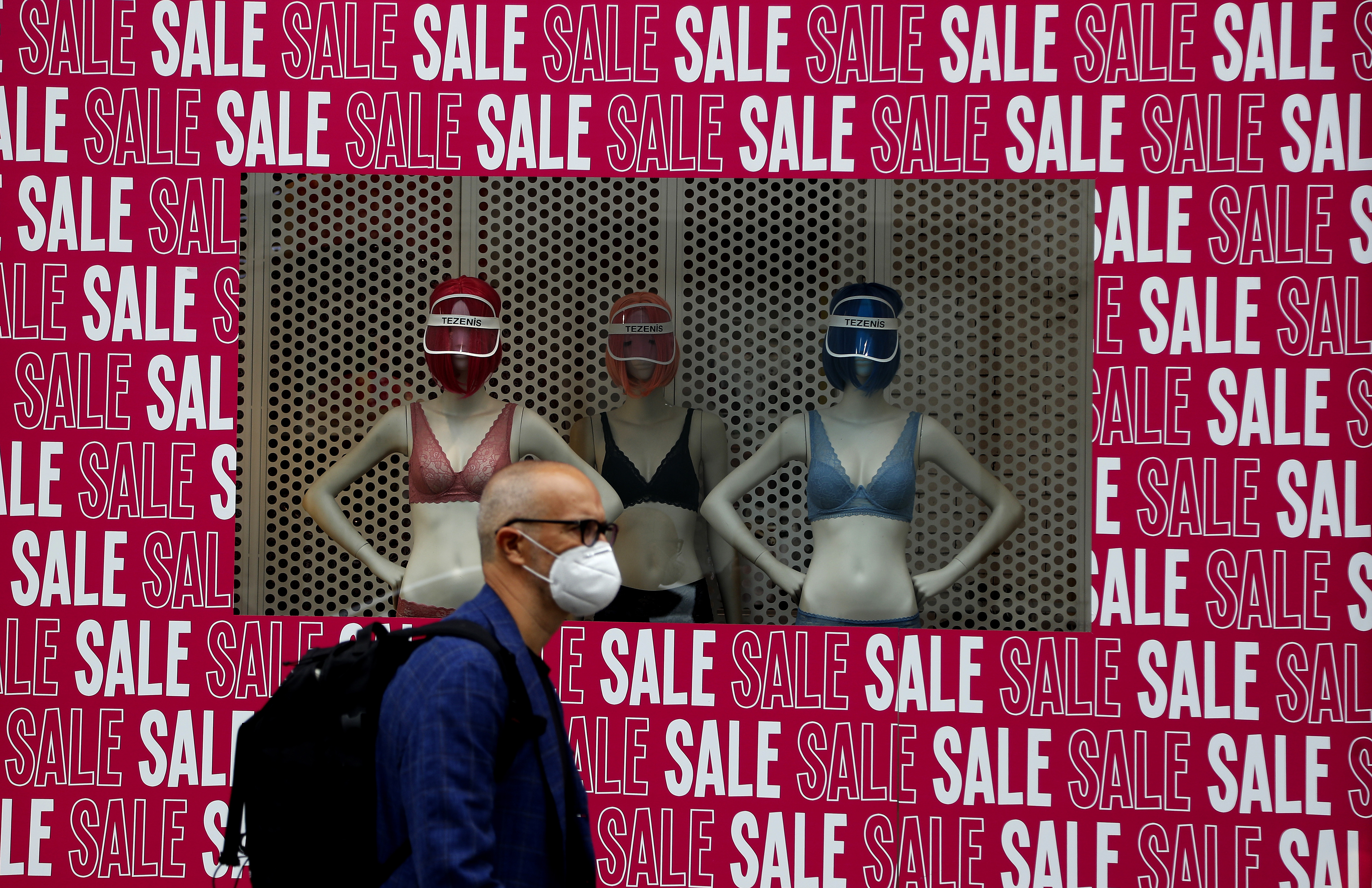 A man wearing a protective face mask walks past a shop window in London, Tuesday, July 14, 2020. Britain's government is demanding people wear face coverings in shops as it has sought to clarify its message after weeks of prevarication amid the COVID-19 pandemic. (AP Photo/Frank Augstein)