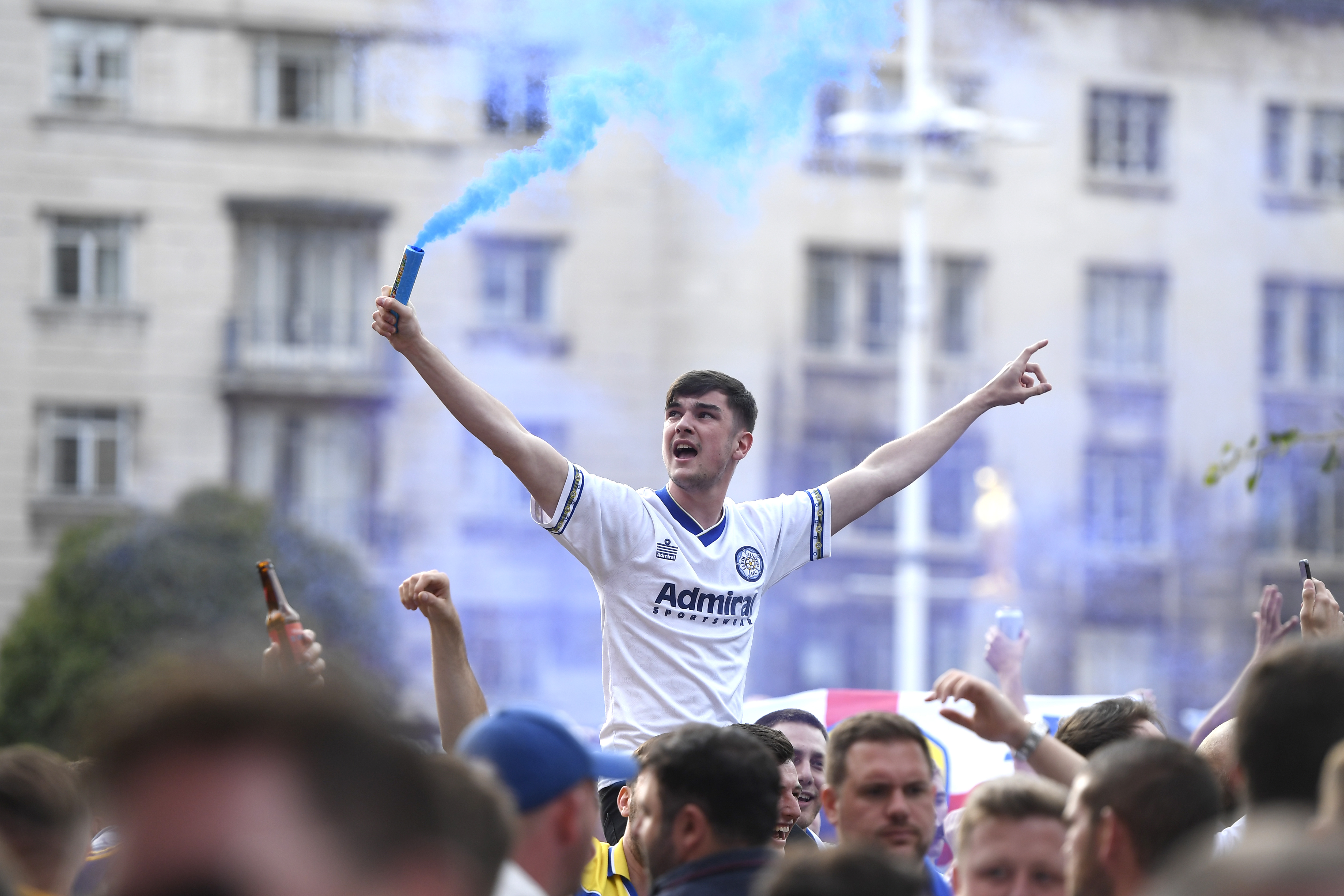 LEEDS, ENGLAND - JULY 19: Leeds United fans celebrate after winning the Sky Bet Championship title at Millennium Square on July 19, 2020 in Leeds, England. (Photo by George Wood/Getty Images)