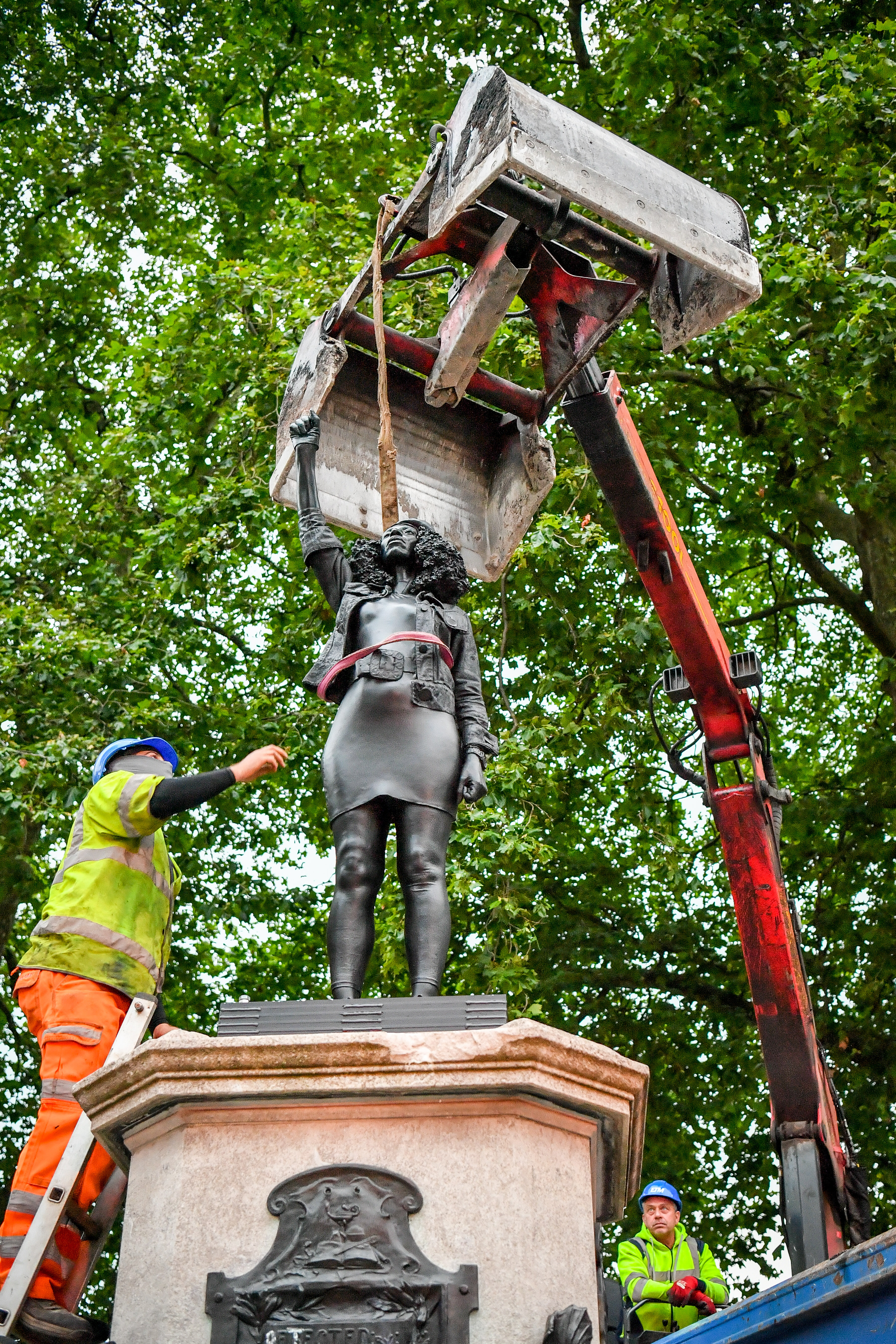 Contractors use ropes to secure A Surge of Power (Jen Reid) 2020, by prominent British sculptor Marc Quinn, which has been installed in Bristol on the site of the fallen statue of the slave trader Edward Colston, as they prepare to remove and load it into into a recycling and skip hire lorry. (Photo by Ben Birchall/PA Images via Getty Images)
