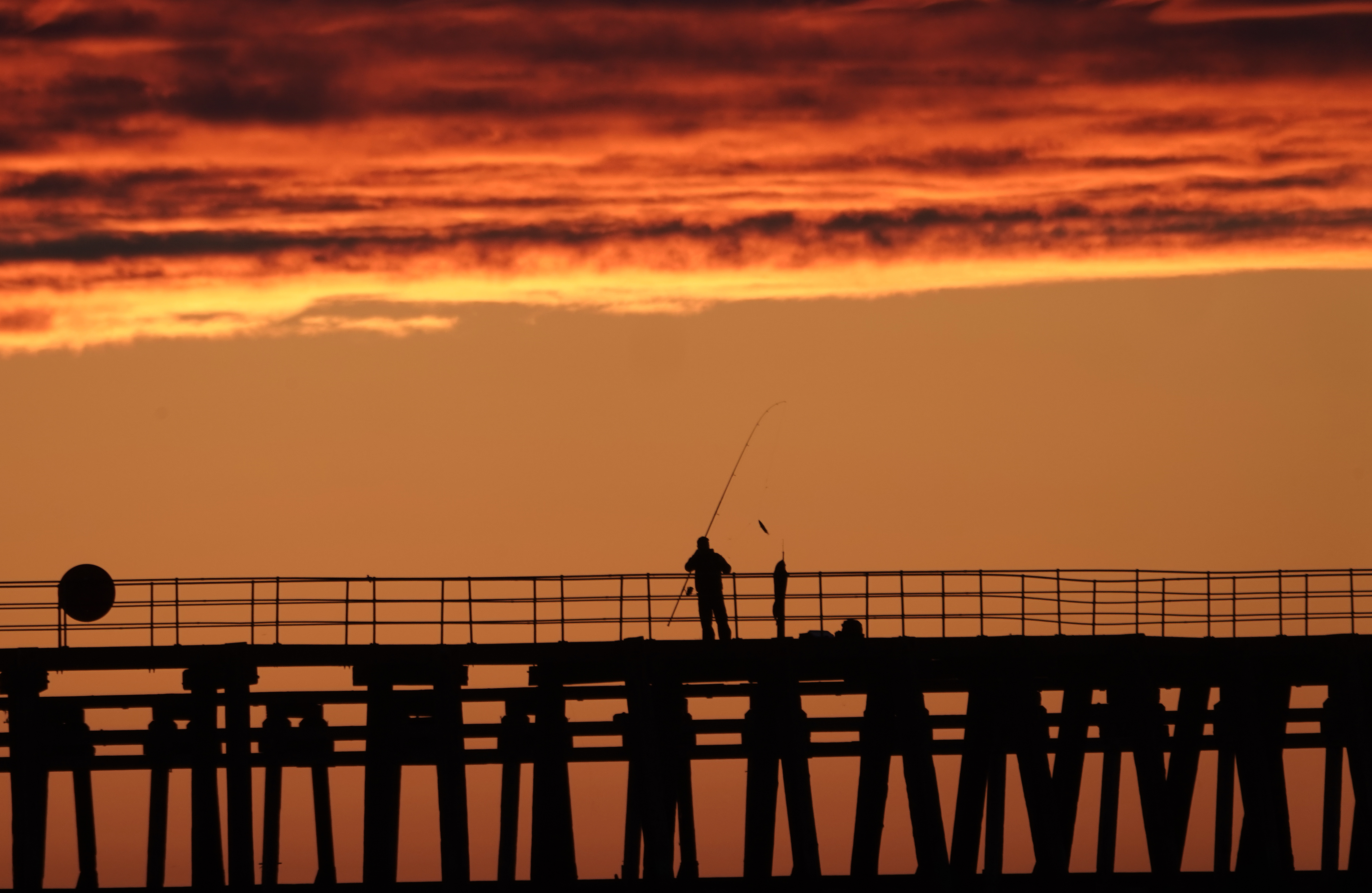 Fishermen on Blyth pier in Northumberland, fishing for mackerel as the sun rises. (Photo by Owen Humphreys/PA Images via Getty Images)